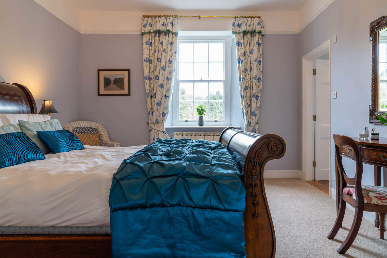 The Blue bedroom in Flear House with king size sleigh bed with matching dresser and bedsides and large sash window overlooking the front garden.