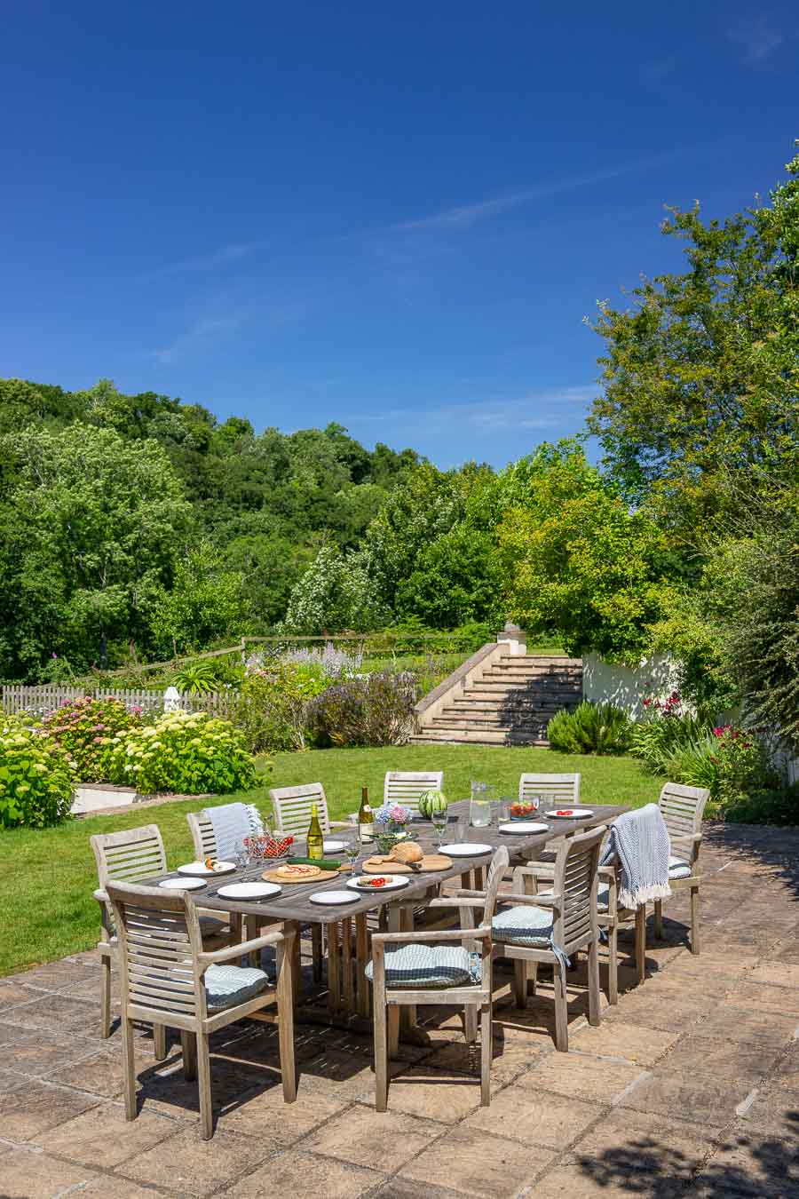 BBQ terrace, large teak table and extensive mature gardens of Flear House Devon.