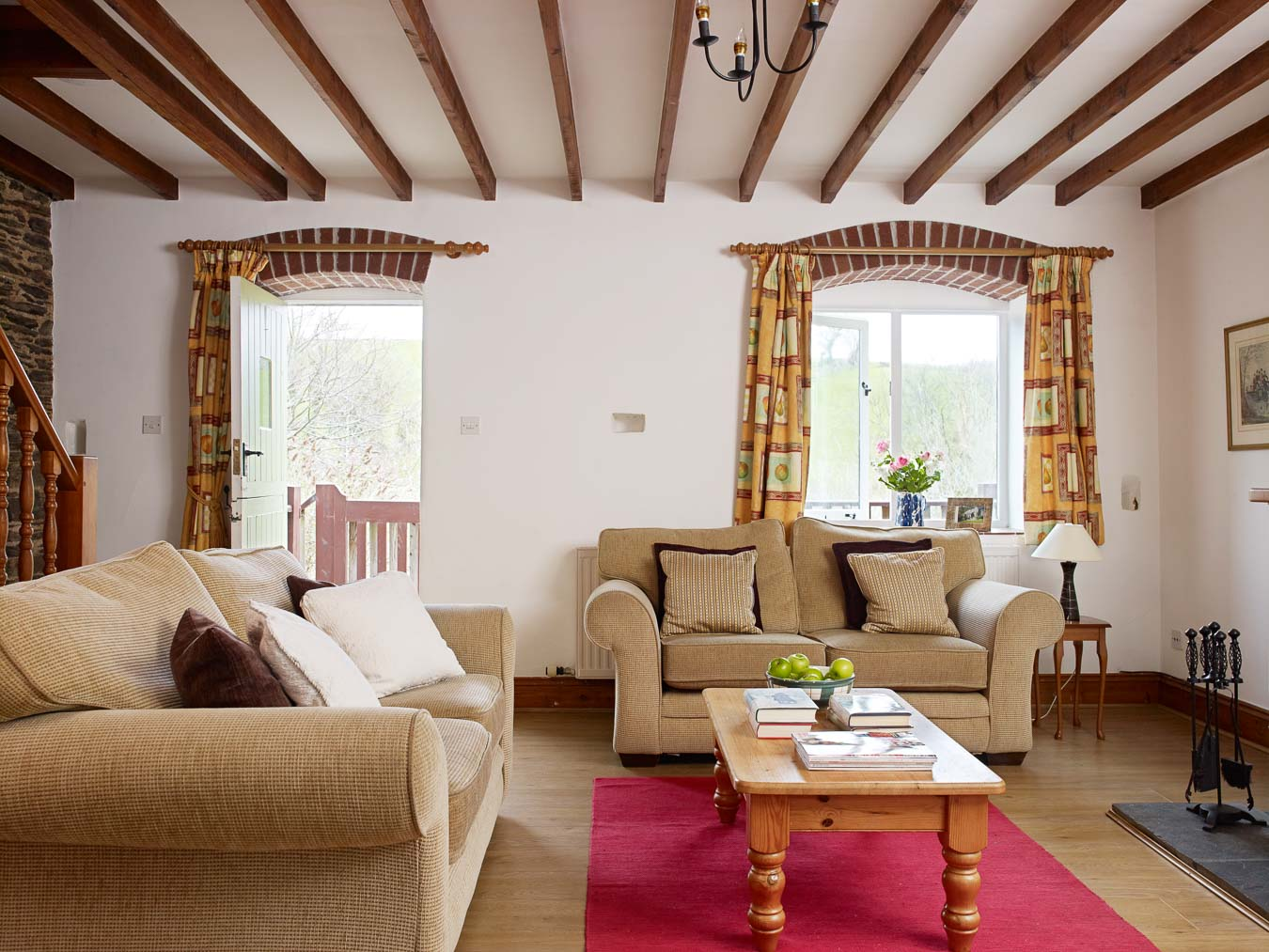 The living room at Cartwheel cottage with open fire and access onto private decking which overlooks the lawn and the Devon hills beyond at Flear Farm.