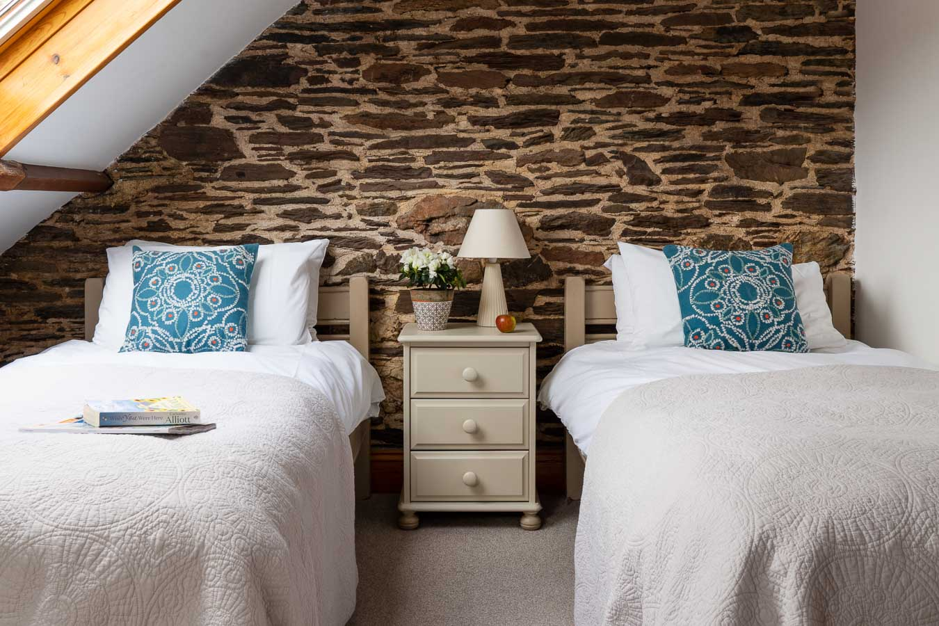 The charming twin room in Cartwheel cottage with exposed brick and soft tones at Flear Farm.