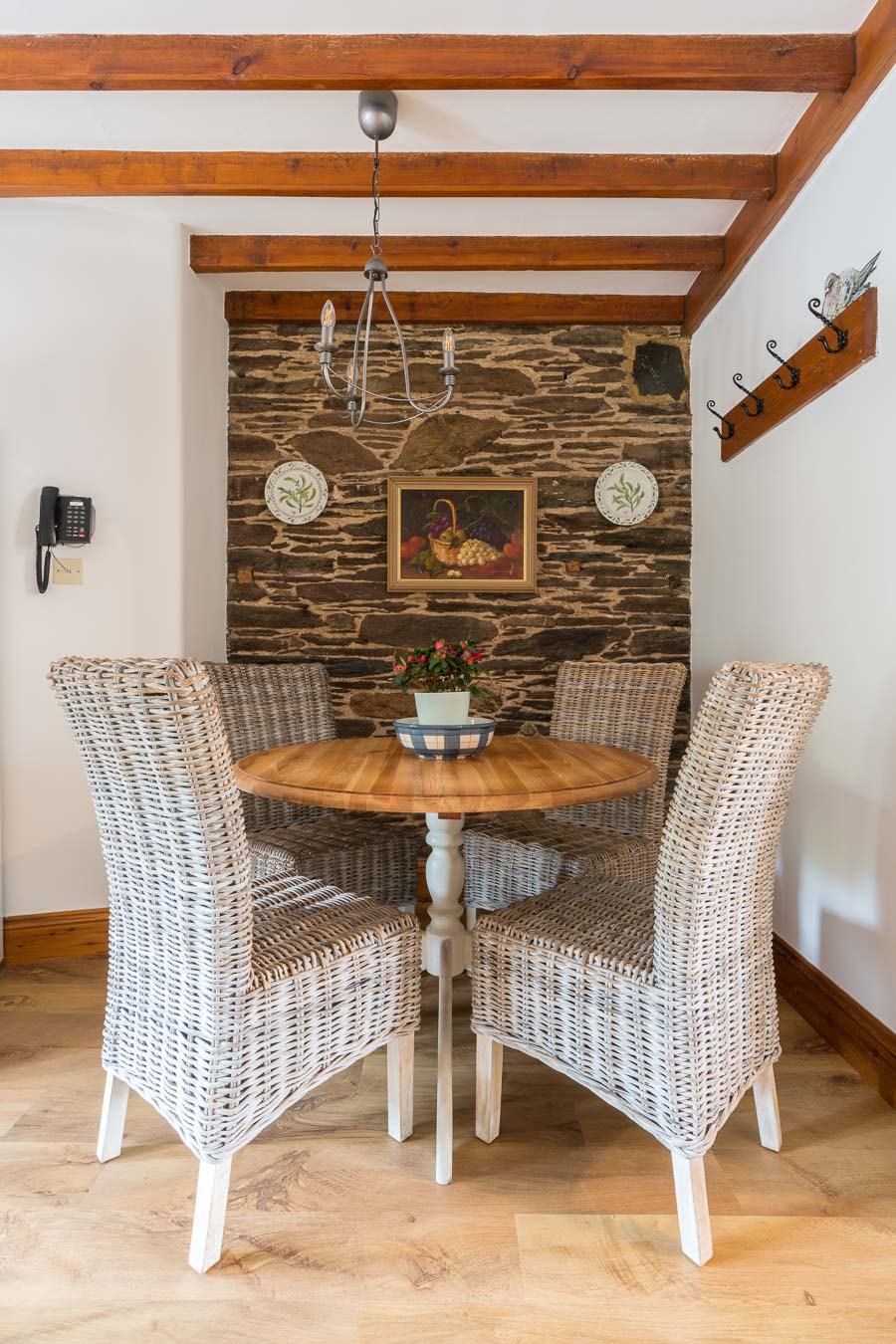 The dining table for four in Cartwheel cottage with wicker chairs and exposed brick work behind.