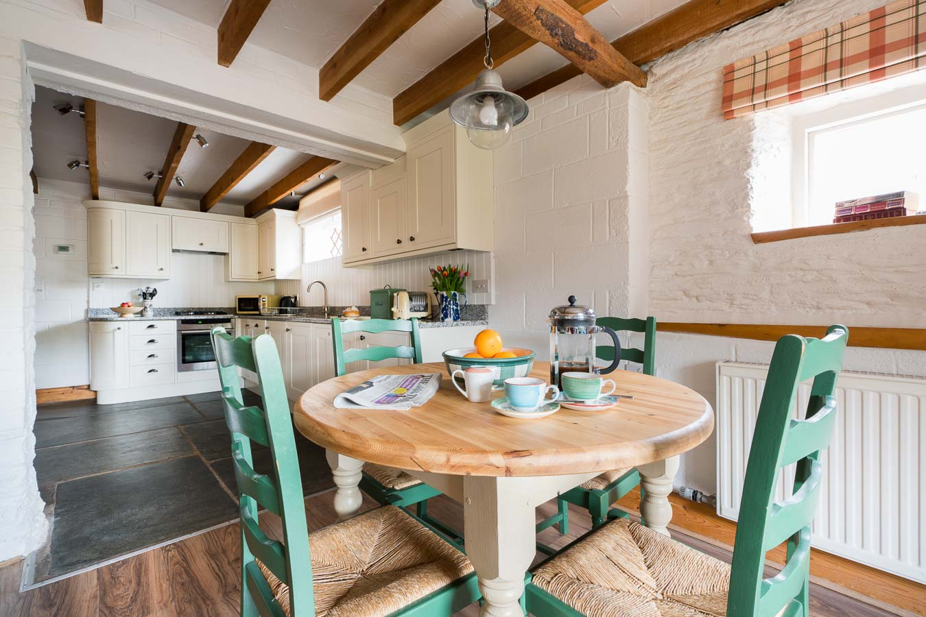 The dining table for four and open archway leading to cream kitchen in Quarry cottage at Flear Farm.