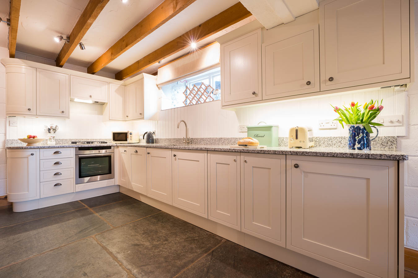 The fresh cream kitchen with granite work tops, Neff oven and original sate floors of Quarry cottage at Flear Farm.