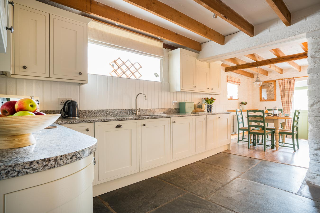 The stylish cream kitchen with granite worktops and slate floor Quarry cottage Flear Farm.