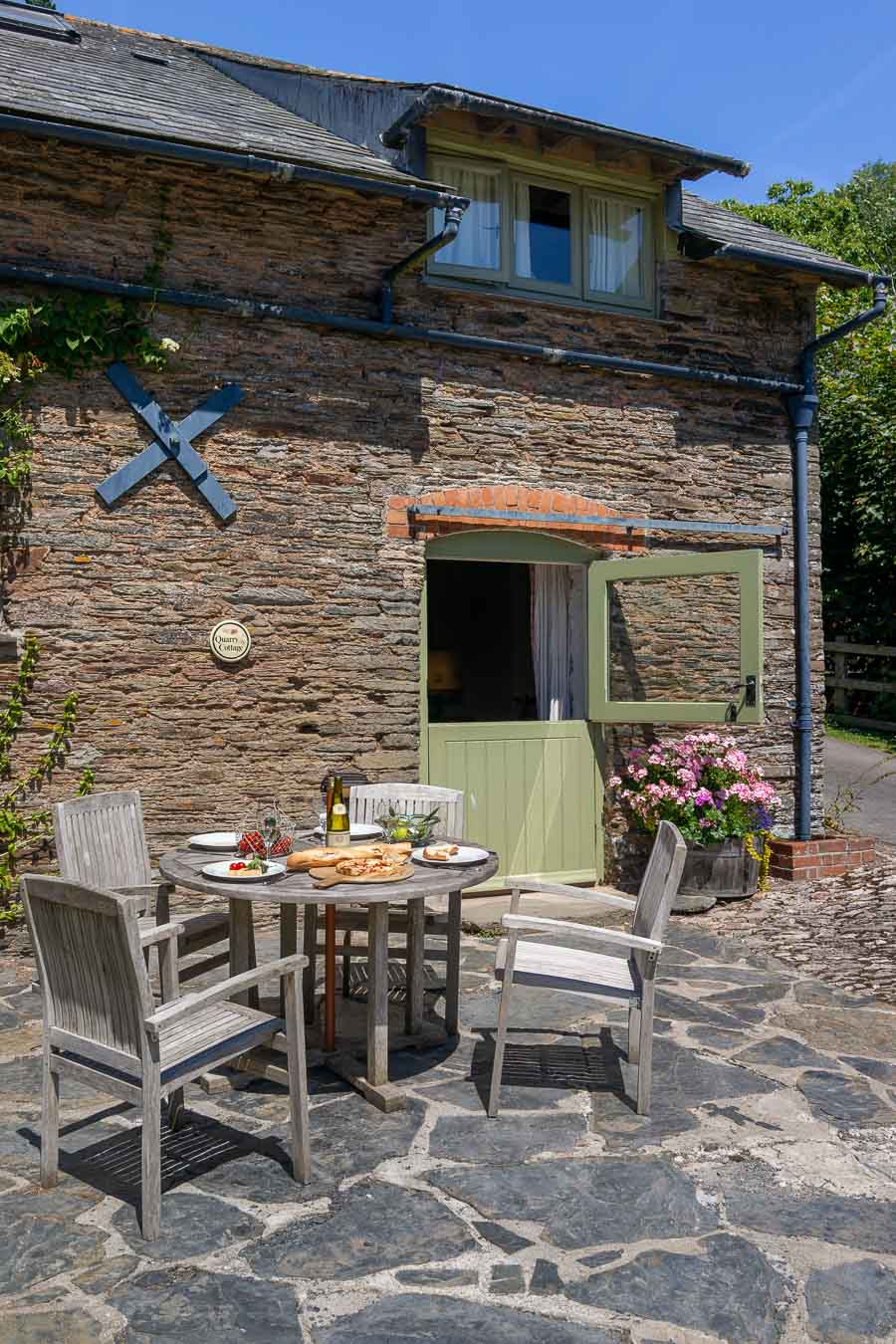 The stable door and original slate and stone of Quarry cottage Flear Farm. With wooden outdoor furniture for four and slate patio area looking onto the rolling green Devon hills.