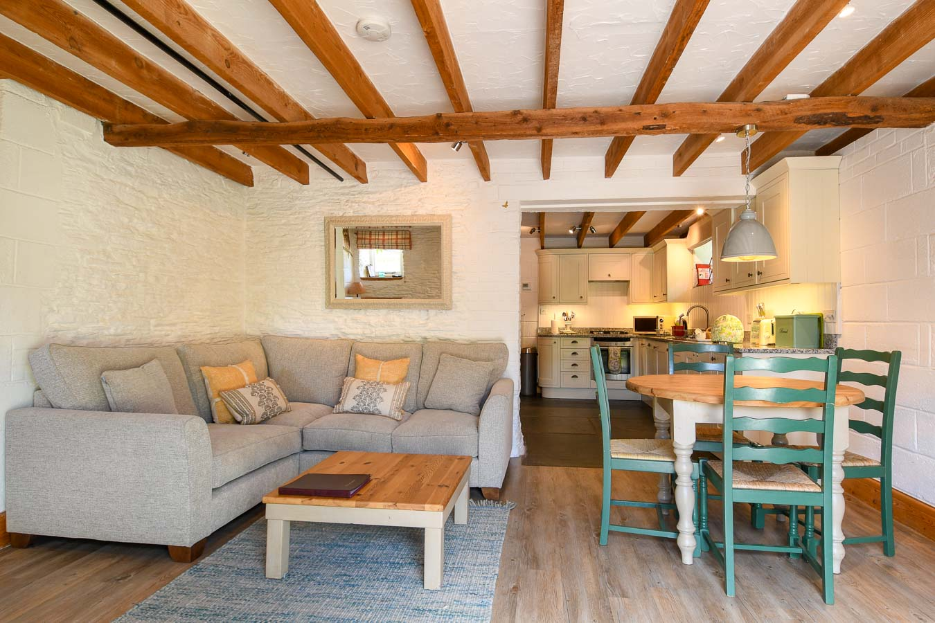 Quarry cottage's open plan living room with fresh colour scheme corner sofa and round table for four at Flear Farm holiday cottages.