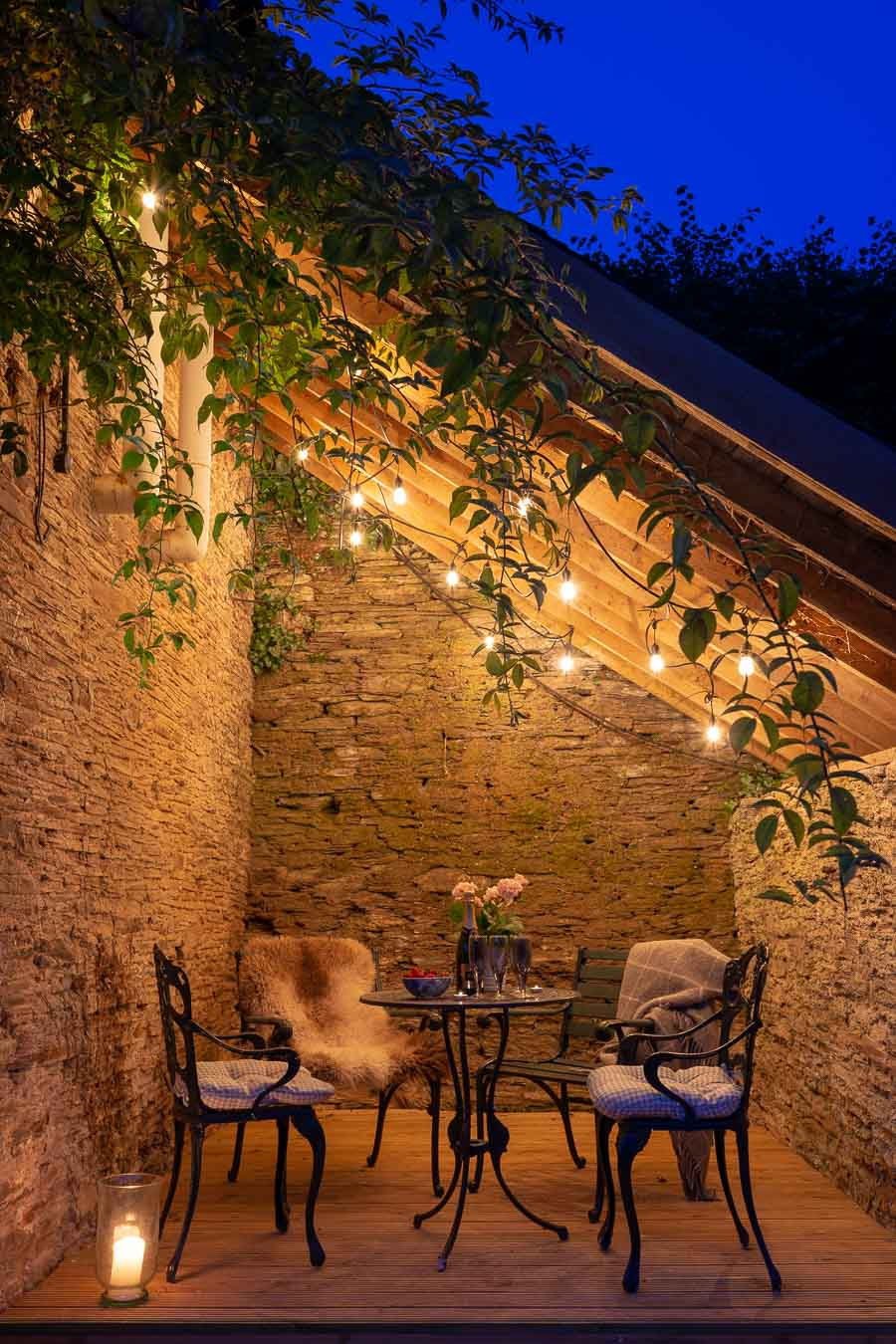 The lean too of the Linhay cottage at Flear Farm with iron furniture and festoon lights.