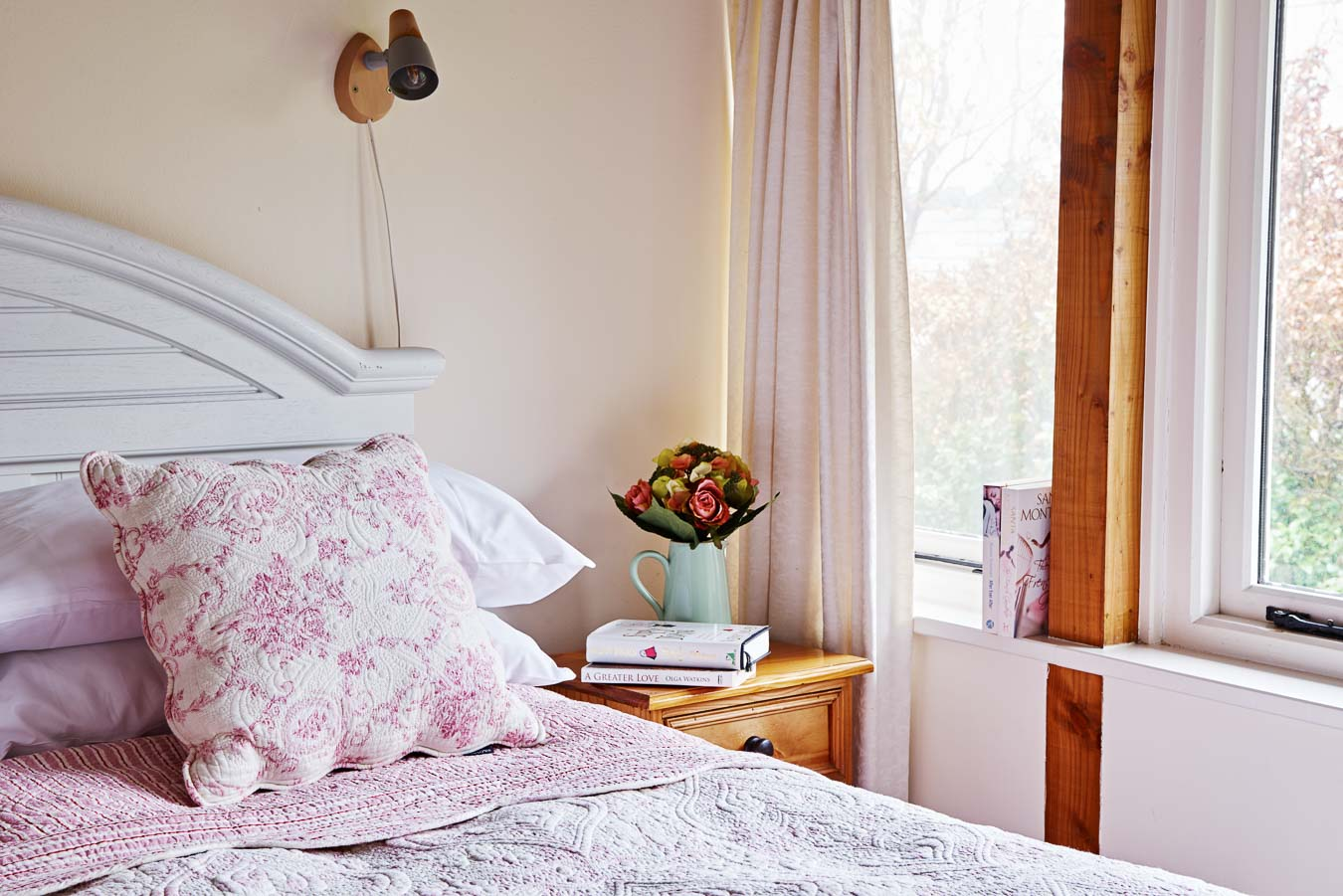 The master bedroom with king size bed in The Linhay cottage Flear Farm. The windows overlook the private garden