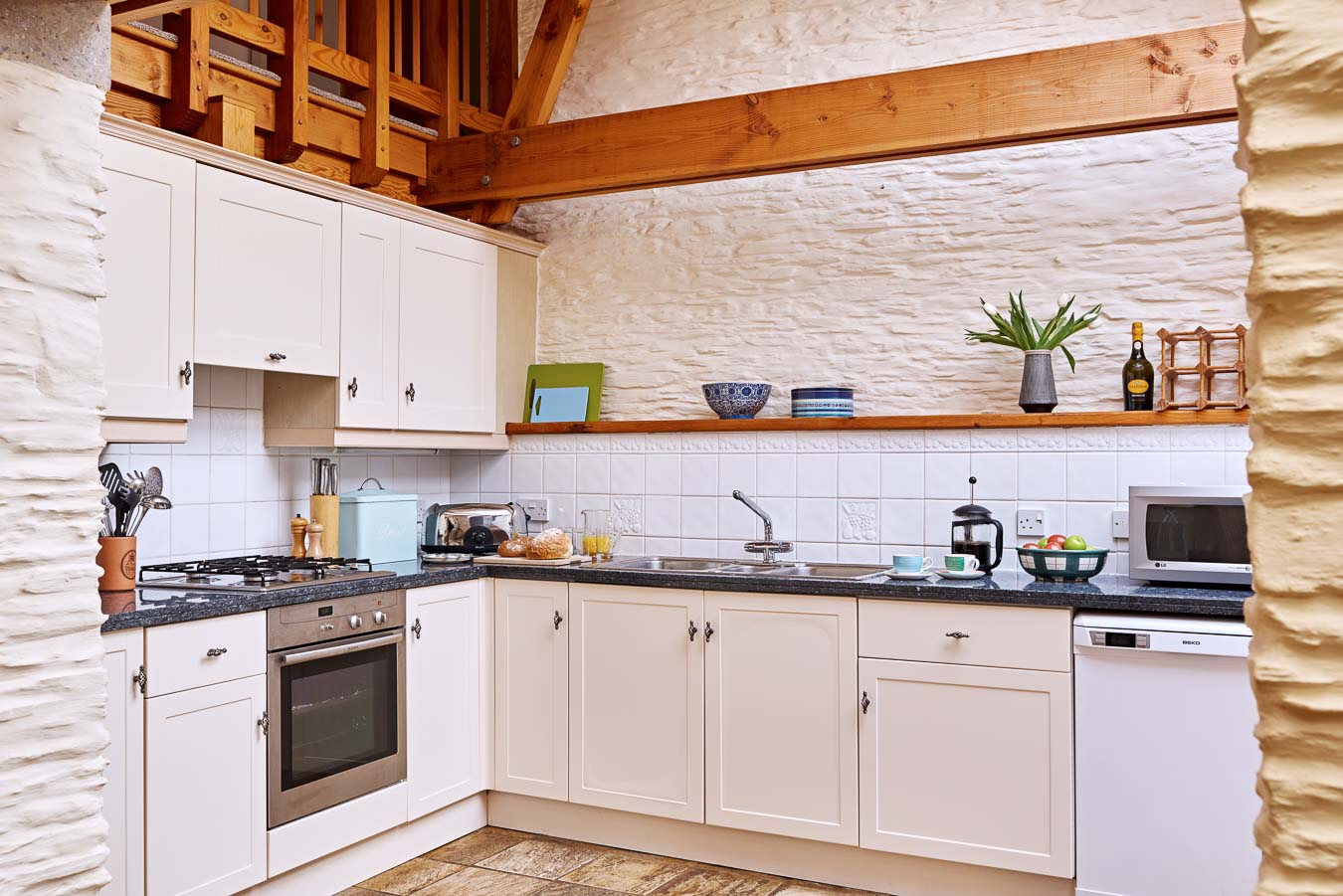 The shaker style kitchen in the Linhay cottage with black granite work tops and heated tiled floor at Flear Farm.