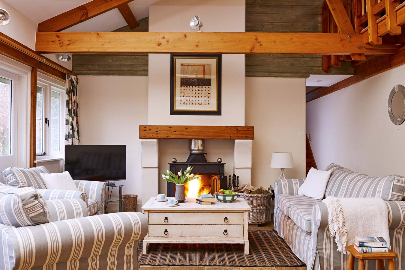 The open plan living room with exposed beams, flat screen TV and log burning stove at The Linhay cottage Flear Farm.