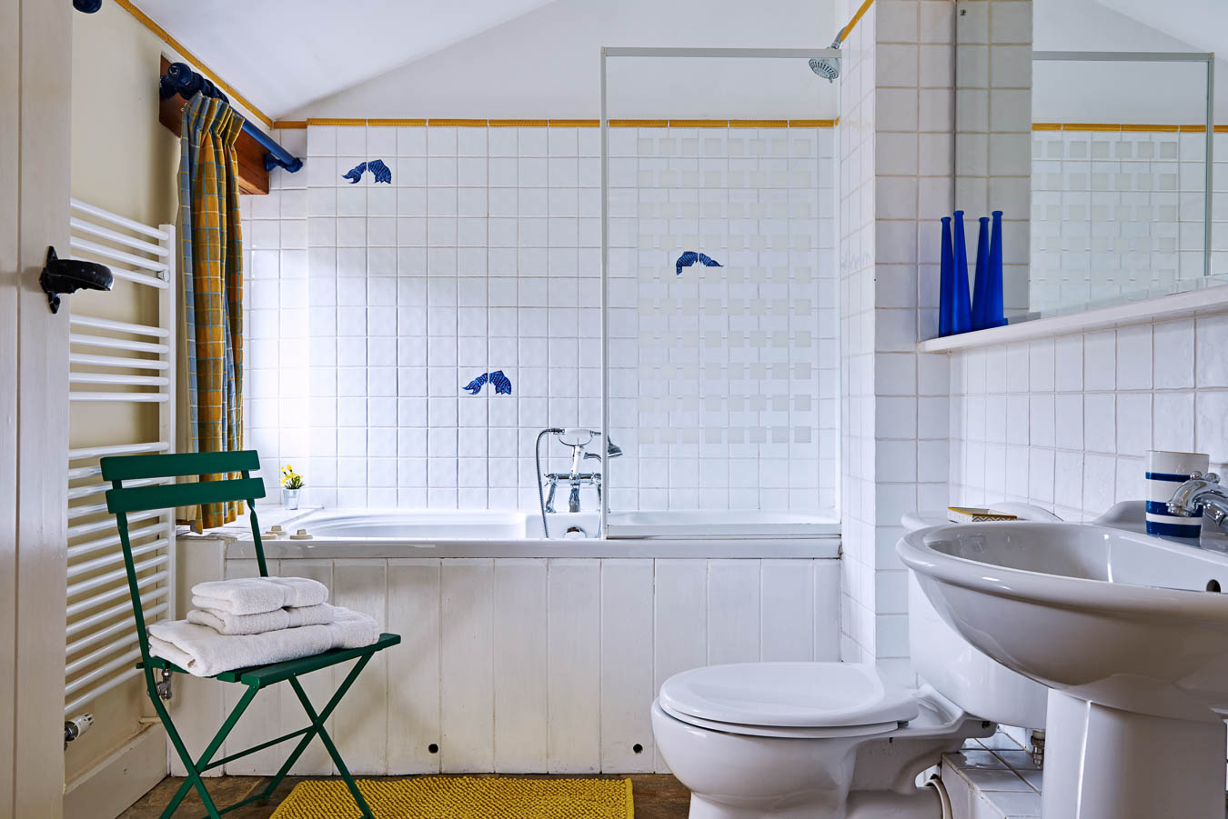 The Linhay cottage Flear Farm master bedroom en suite with chrome bath accessories and blue and yellow theme.