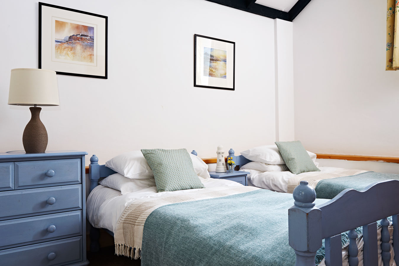 The first floor twin room in The Linhay cottage Flear Farm with blue painted beds and en suite bathroom with shower.