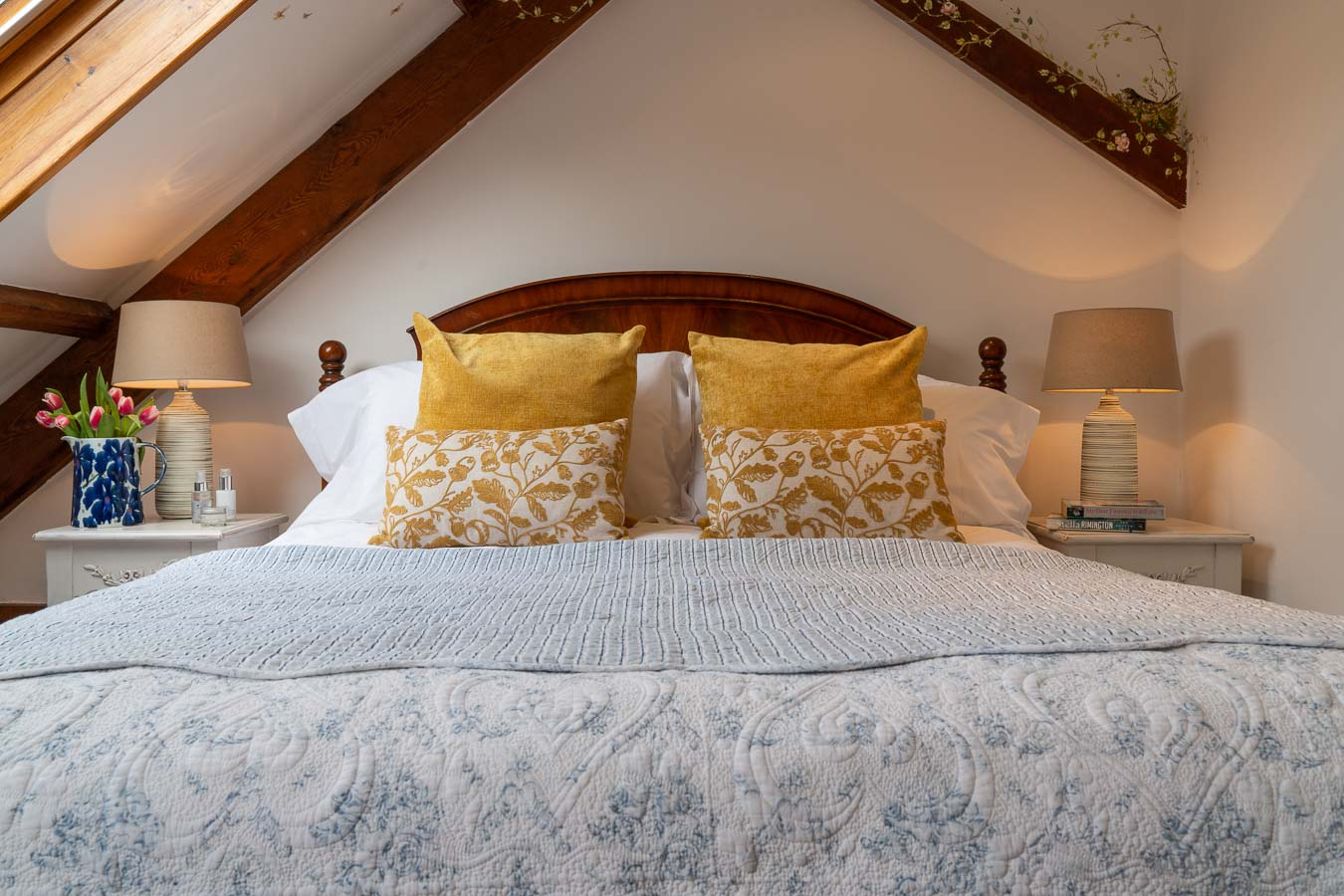 The gorgeous master bedroom, with mahogany bedhead and sumptuous bedding and cushions. Mangers cottage Flear Farm Devon.