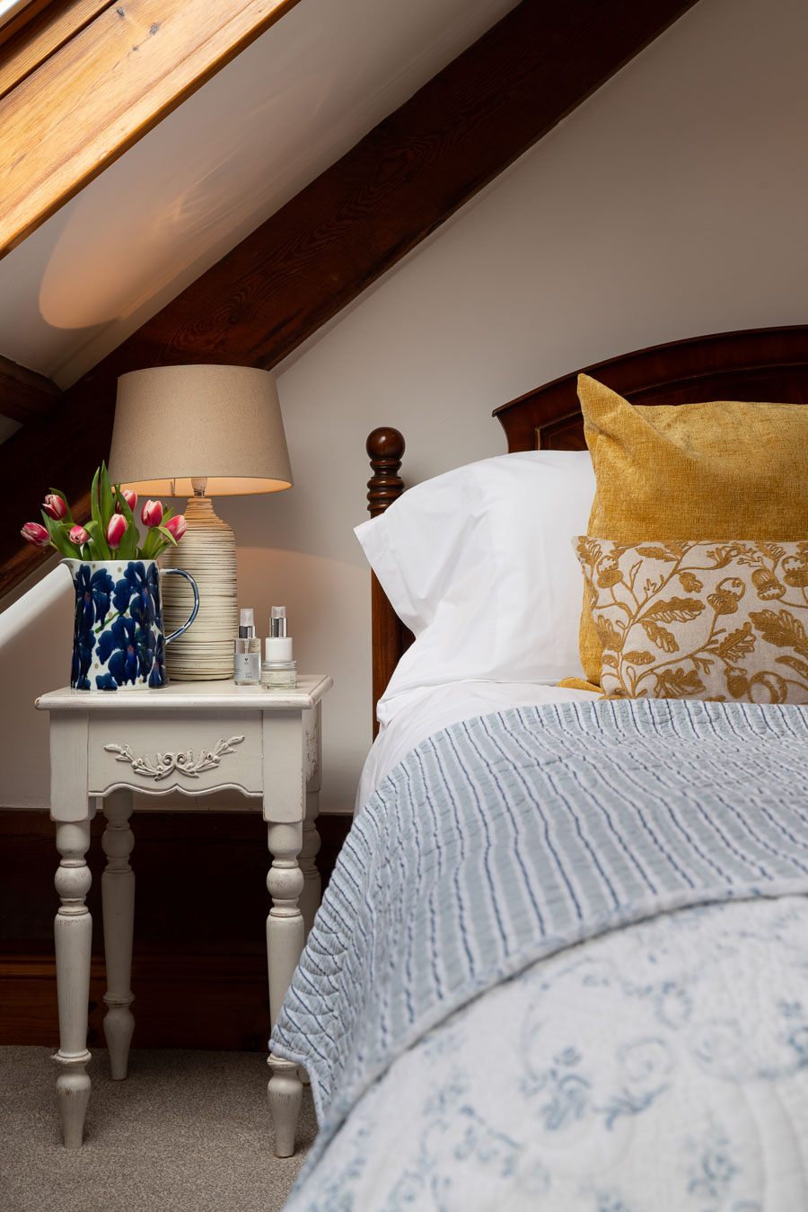 Blue bedspread and yellow cushions on the Master bed in Mangers cottage Flear Farm.