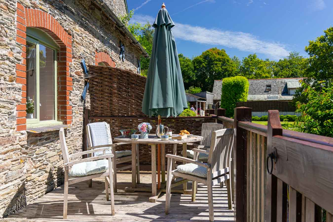 The private south facing sun terrace of Mangers cottage Flear Farm. Outdoor furniture and green views of Devon countryside.