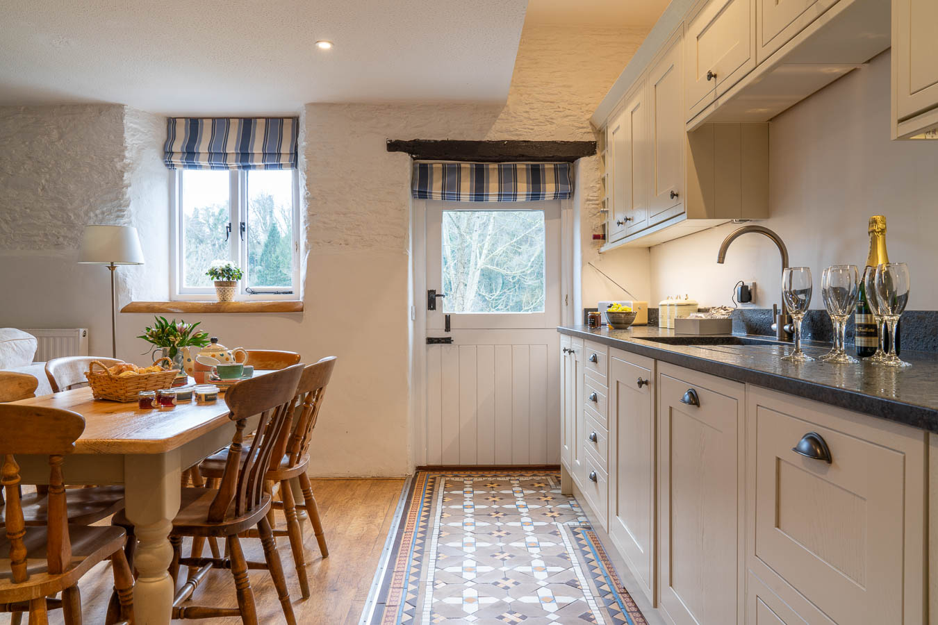 The well appointed Kitchen in The Sables Cottage at Flear Farm. With charming floor tiles and granite work tops the stable door looks out onto the private garden.