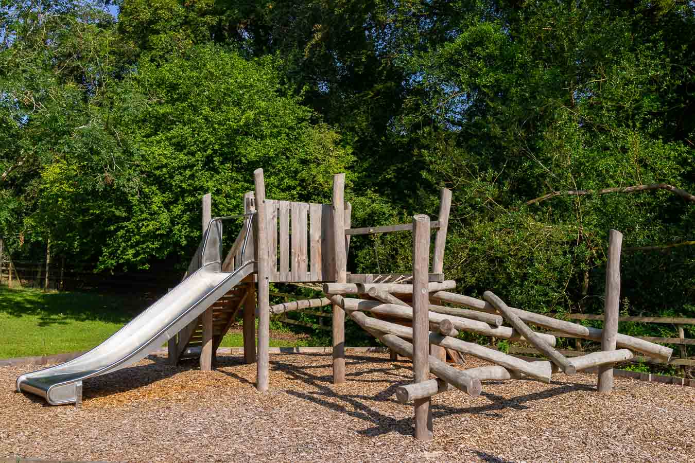 The natural playscape log pile climbing frame and slide in the outdoor playground