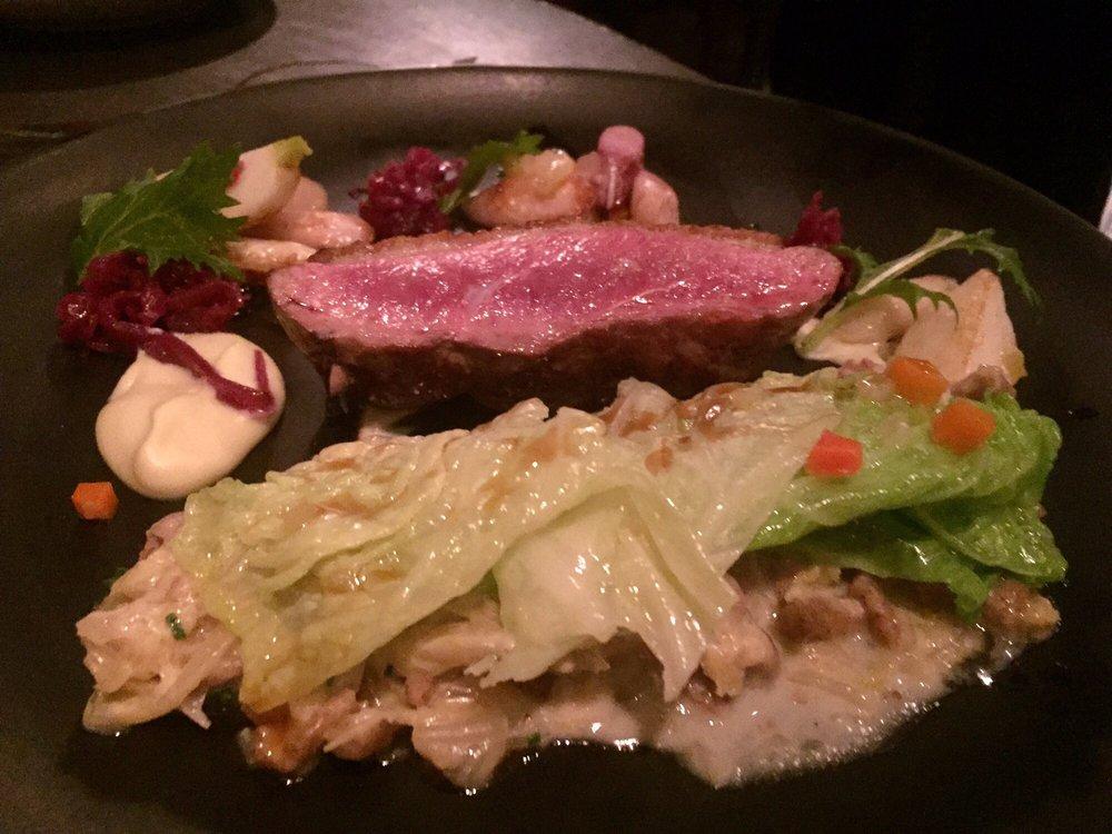 Braised Savoy Cabbage, Pickled Kumquat, Garlic  Duck  Sausage, Savory Millet Cake, Coriander Jus