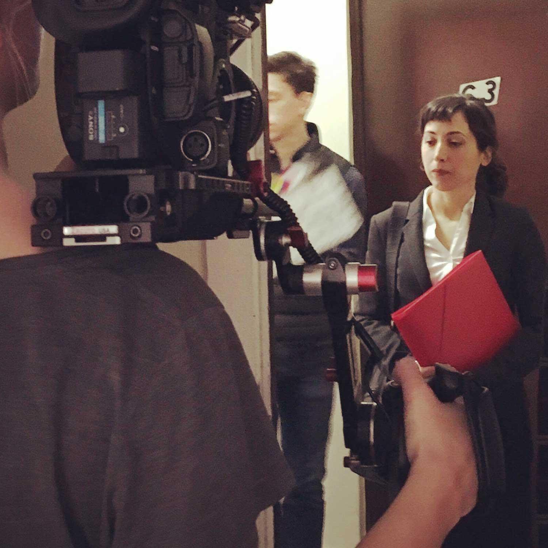 Amanda dressed in business suit filming a short film