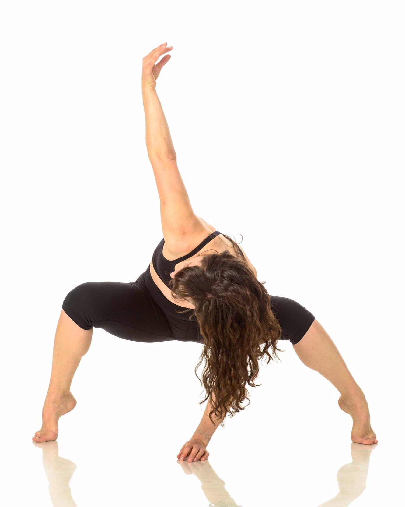 Amanda in black sports bra and legs, in an off kilter plie, one arm up one arm down, face obscured by long curly brown hair.