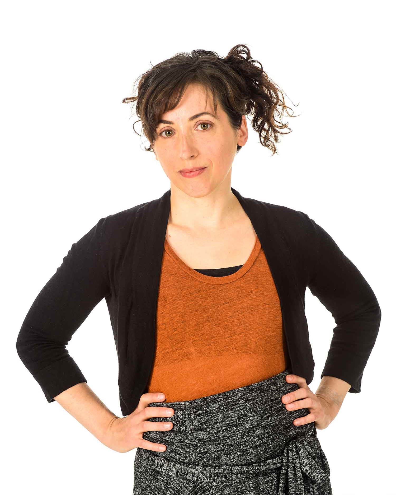 Amanda standing with hands on hips - hair is up, black sweater, rust top, grey skirt.
