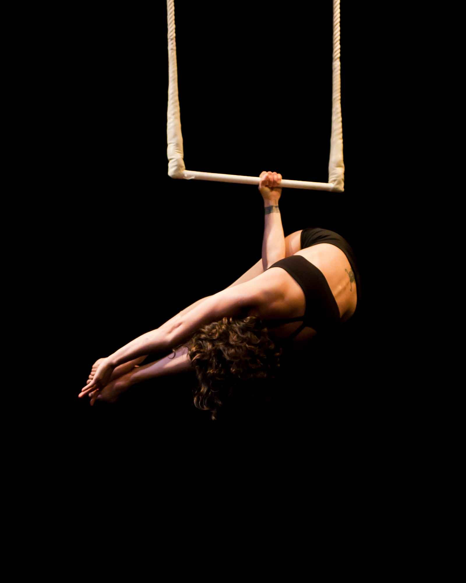 Amanda in meathook position on trapeze with dark background, and black top and shorts.