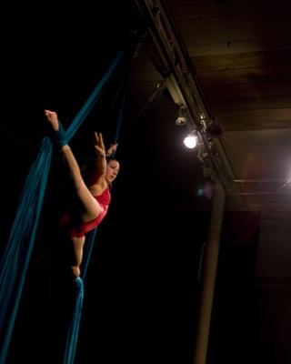 Amanda in red leotard doing splits on teal silks