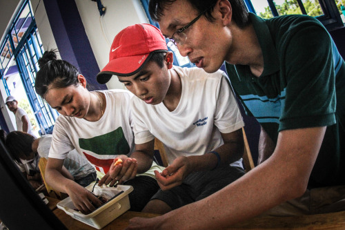 Quốc (right) participates in training for the LEGO robotics workshop with fellow volunteers. (Photo: Antonio F Delgado)