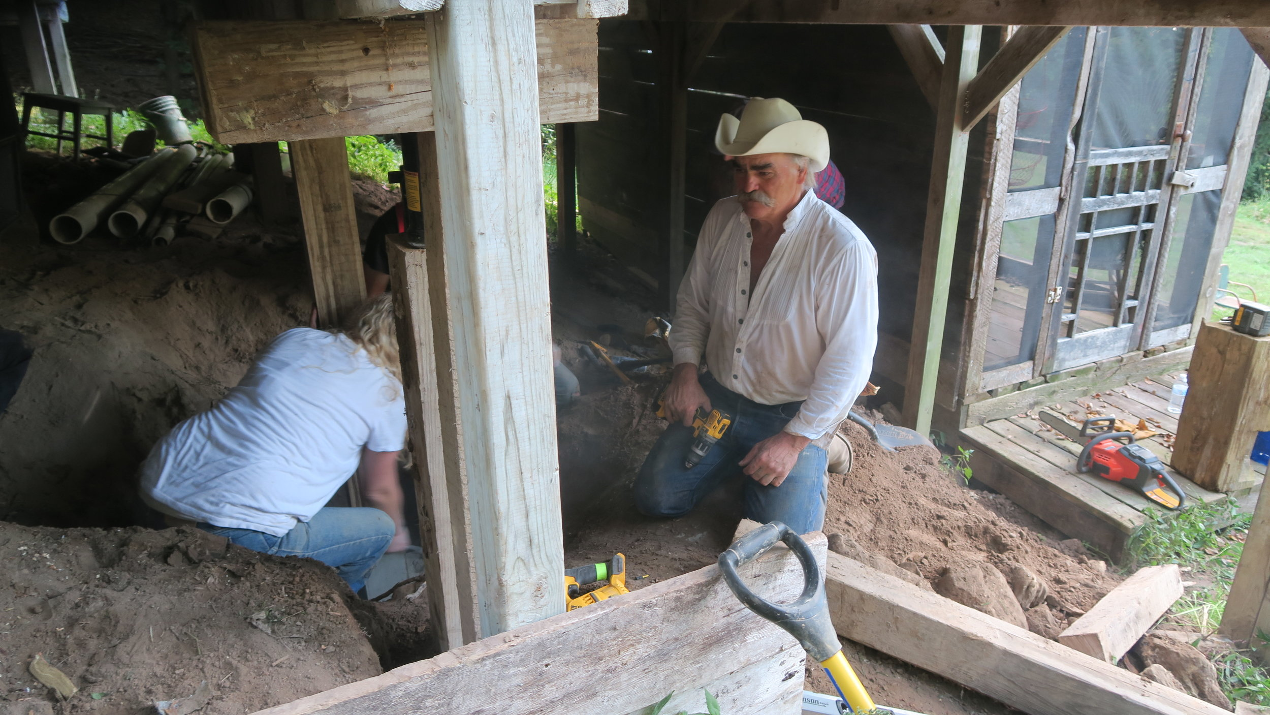 Marty Raney right, helps shore up support beams under the house. Photo by Natalie Munio