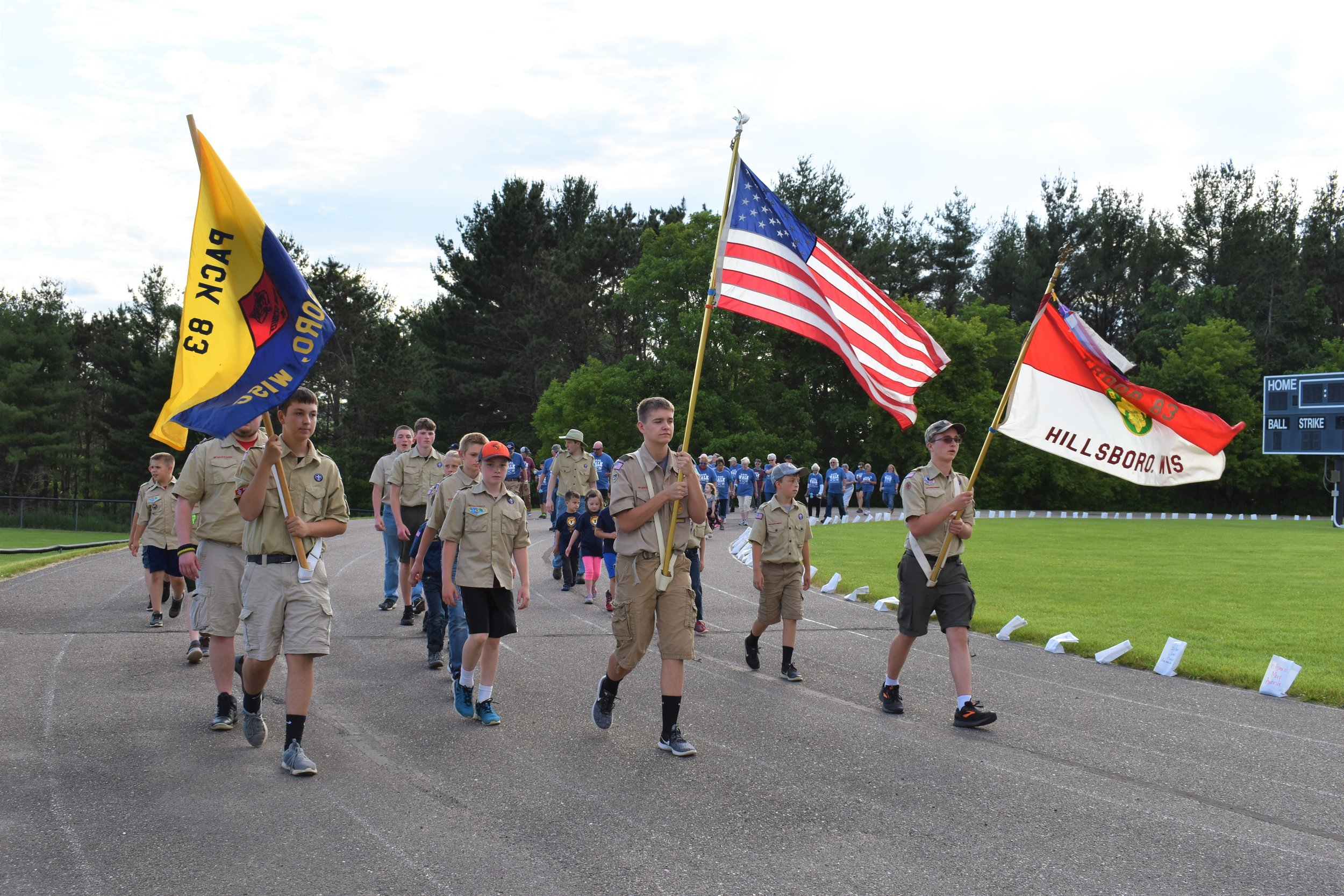 Front l to r- Nathan carrying the Pack 83 flag, Niles carrying the United States flag, and Ethan carrying the Troop 83 flag, lead survivors in opening lap