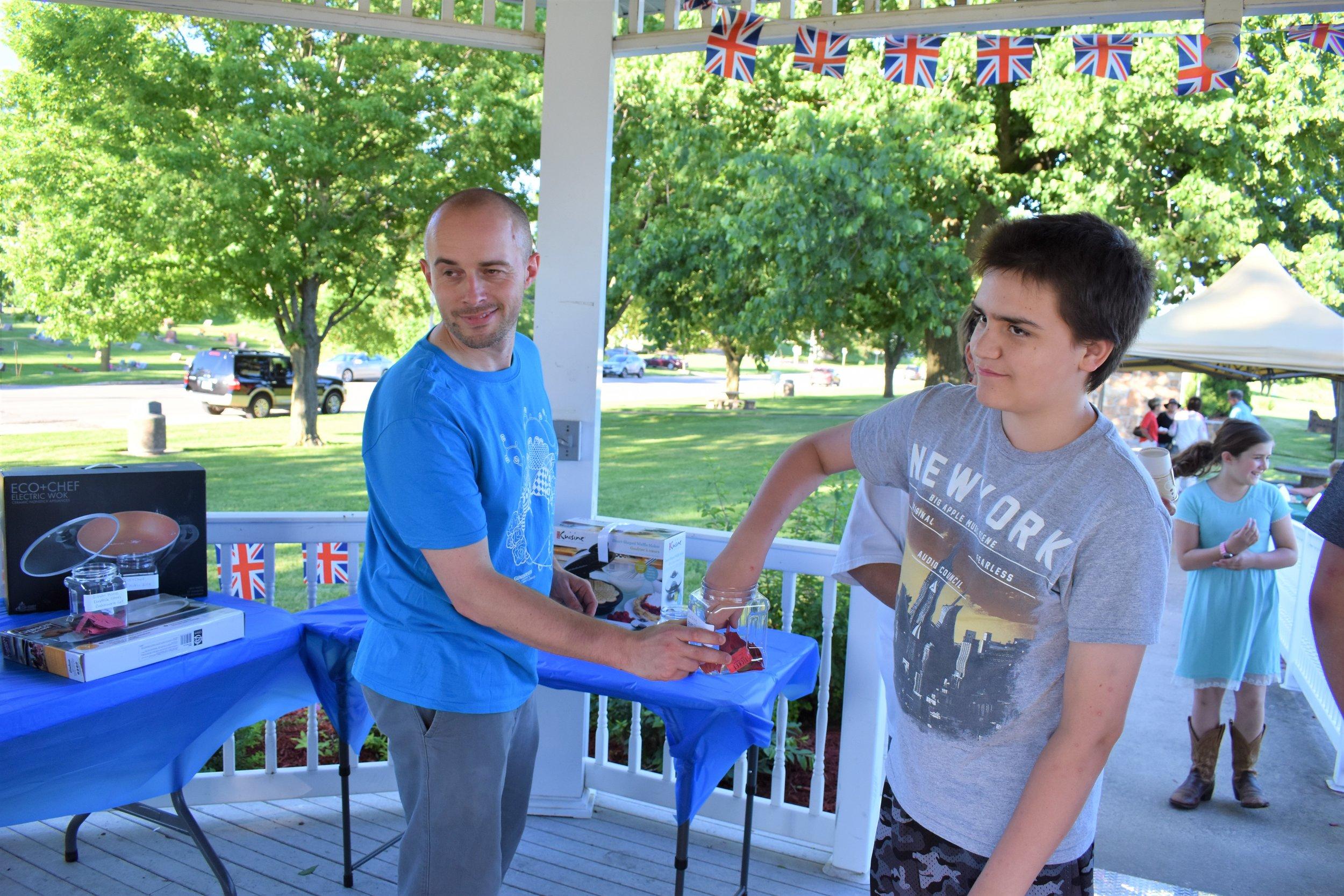 Dan Howard has Nathan Smalley draw the winning raffle tickets