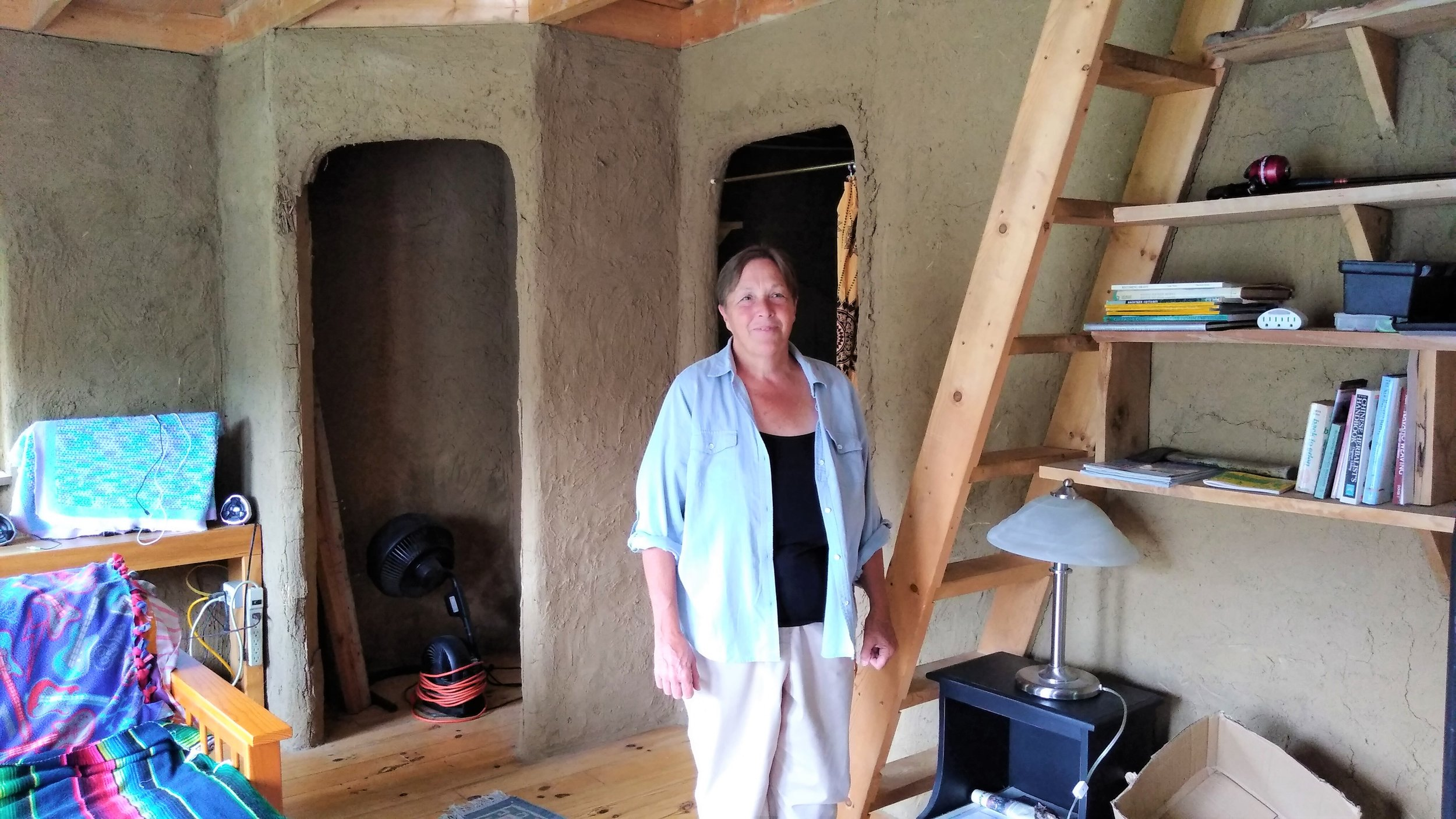 Dena inside one of the houses that is made of clay and straw