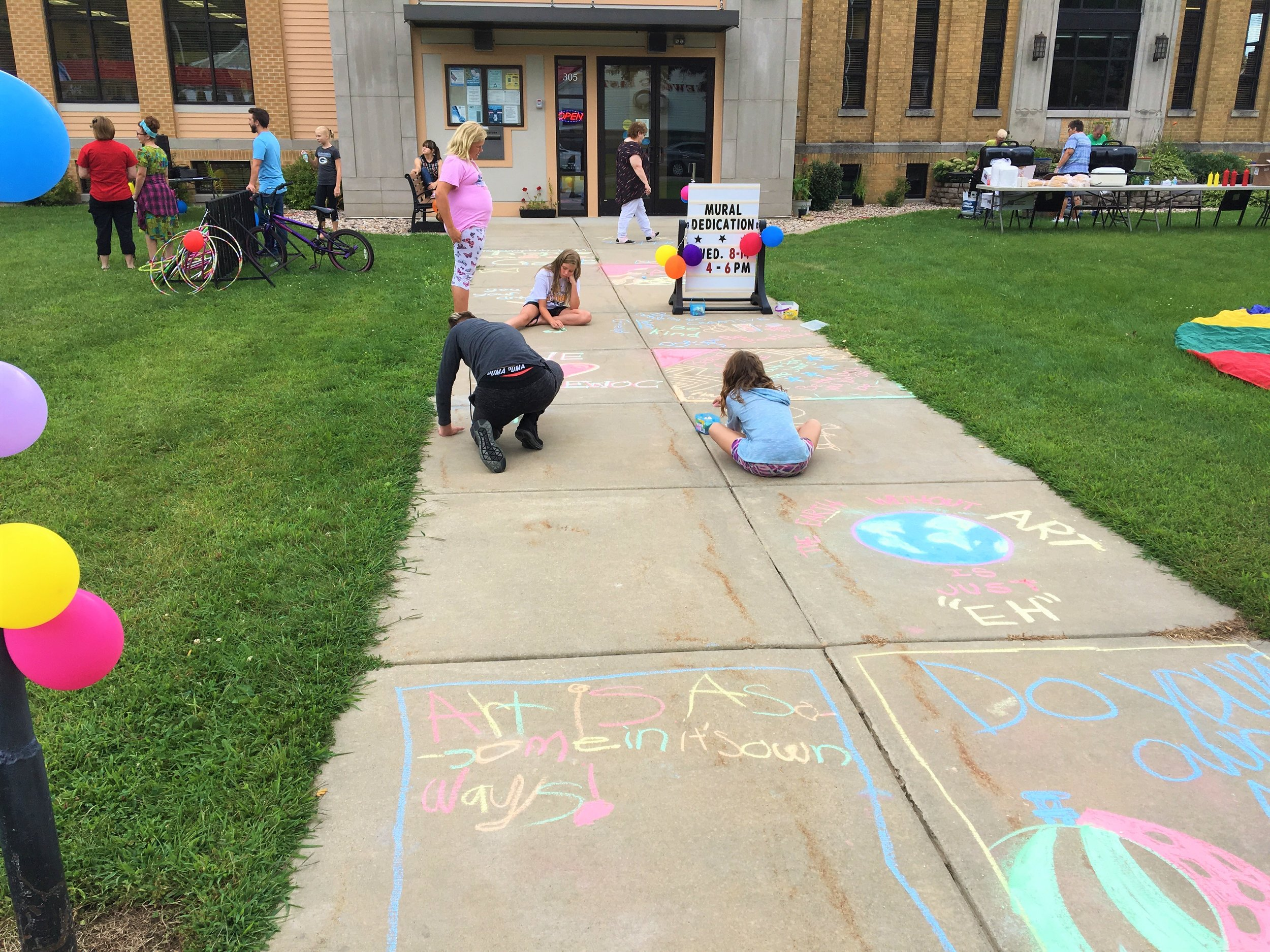 Children create sidewalk art at mural dedication