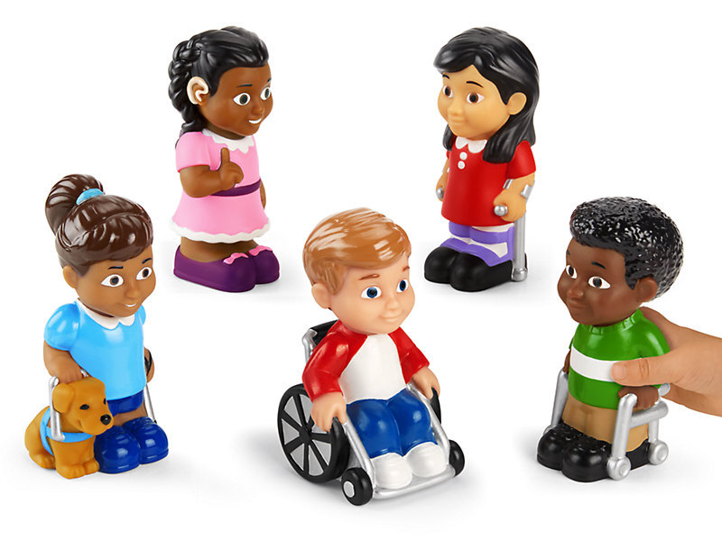 [Image Description: Five soft dolls of varying abilities. The doll to the far left has light brown skin and brown hair in a pony tail. They have a service dog. The second doll from the left has medium brown skin and black hair done up in braids. They have a hearing aid and are using sign language. The middle doll has light skin and short red hair. They are using a wheelchair. The second doll from the right has tan skin and straight black hair and they are using arm crutches. The doll to the far right has dark brown skin and short curly black hair. They are using a walker.]