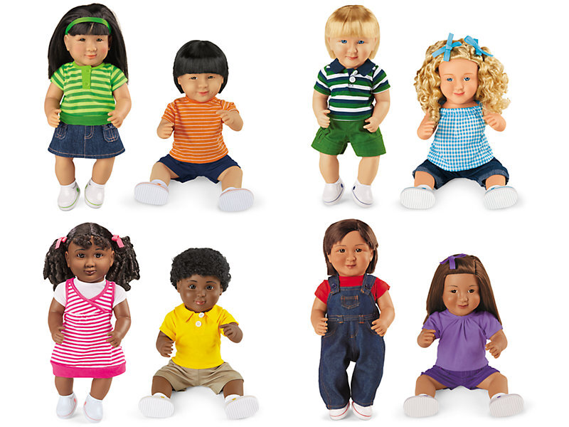 [Image Description: Eight hard dolls. Top Left: Two asian-coded dolls. The doll to the left has long straight black hair, a green headband, a green striped shirt, a denim skirt, and white shoes. The one to the right has short straight black hair, and orange striped shirt, denim shorts, and white shoes. Top Right: Toe caucasian-coded dolls. The one to the left has short blonde hair, a blue, green, and white striped polo shirt, green shorts, and white shoes. The one to the right has curly blonde hair with two blue bows in it. They are wearing a blue and white gingham shirt, denim shorts, and white shoes. Bottom Left: Two Black-coded dolls. The one on the left has curly dark brown hair in pigtails with two pink bows. They are wearing a white and pink striped dress, and white shoes. The doll on the right has short curly dark brown hair. They are wearing a yellow polo shirt, khaki shorts, and white shoes. Bottom Right: Two hispanic-coded dolls. The doll on the left has short brown hair, a red t-shirt, denim overalls, and white shoes. The doll on the right has long brown hair with a purple bow. They are wearing a light purple t-shirt, dark purple shorts, and white shoes.]