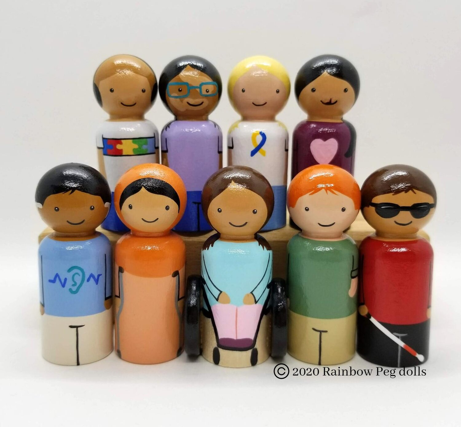 [Image Description: Nine peg dolls of varying abilities. From the top left to bottom right there is a doll with autism, vitiligo, a yellow and blue ribbon (could not find the significance of this), a cleft palate, hearing aids, crutches, a wheelchair, a smaller arm, and blindness.]