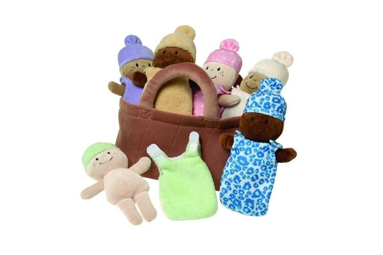 [Image Description: A brown plush fabric basket with four soft baby dolls of varying skin tones inside of it. They are all wearing sleep sacks of varying colors. There are also two baby dolls outside of the basket. The one on the left is naked and next to it is it's green removable sleep sack.]