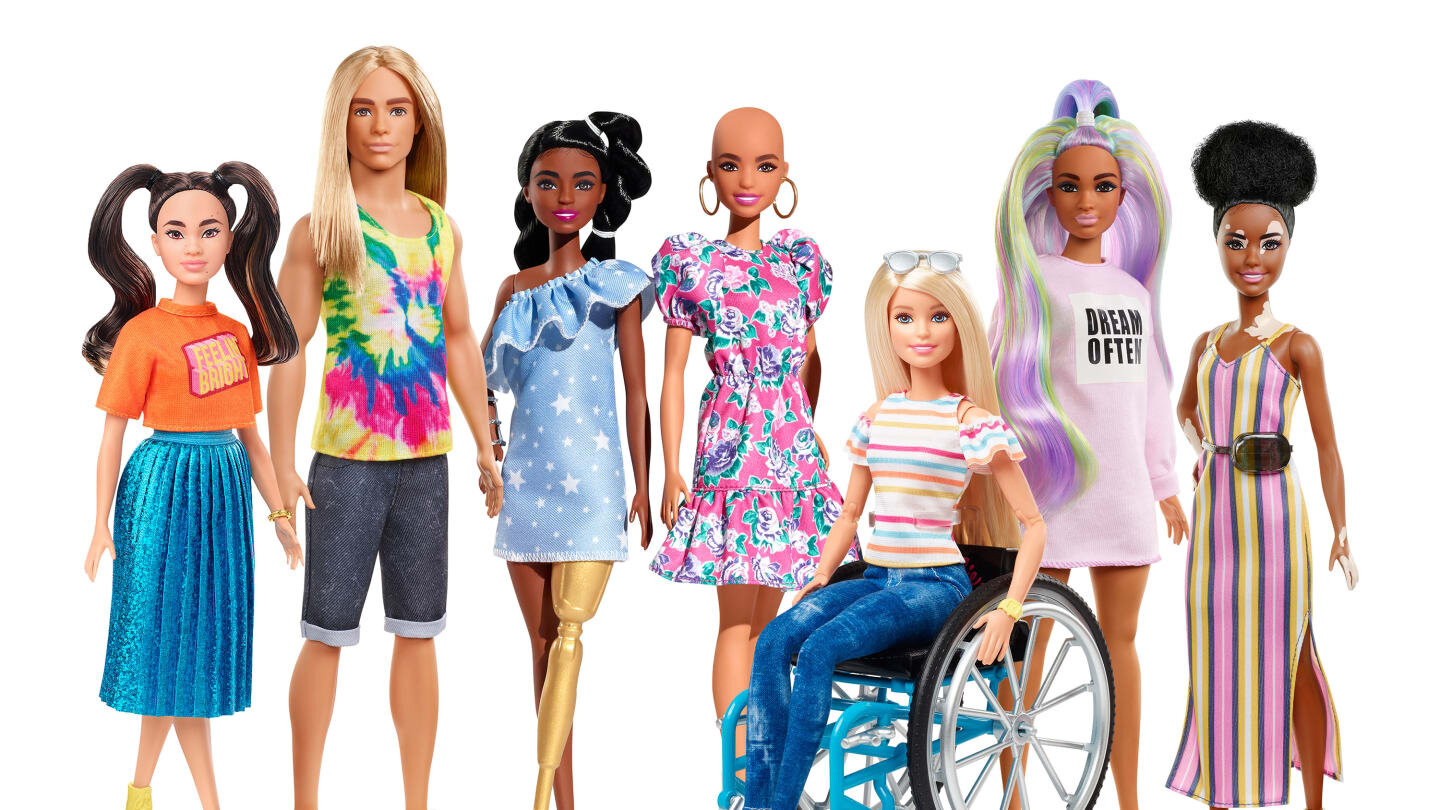 """[Image Description: Seven Barbie dolls. From left to right: A short, asian-coded doll with dark brown hair in high pigtails. They wear an orange crop top that reads """"Feelin' Bright"""" and a long metallic blue pleated skirt. The second doll from the right is male-coded. They are tall and light skinned with straight long blonde hair. They wear a tye-dye tank top and denim Bermuda shorts. The third doll from the right is medium height. They have dark brown skin and black hair which is done in two pigtails. They are wearing a light blue dress with star detailing. They also have a gold prosthetic leg. The middle doll is medium height. They have medium skin and no hair. They are wearing a pink dress with floral detailing and gold hoop earnings. The third doll from the right is medium height with light skin and long straight blonde hair. They are using a wheelchair and they are wearing a white t-shirt with colorful stripes and blue jeans. The second doll from the right is medium height and has medium brown skin and colorful streaked wavy hair. They are wearing a long-sleeved dress that reads """"Dream Often"""". The doll on the far right is short and has dark brown skin wth vitiligo. They have black hair tied back in a poof on the top of their head. They wear a striped pink, white, and yellow dress and a brown fanny pack.]"""