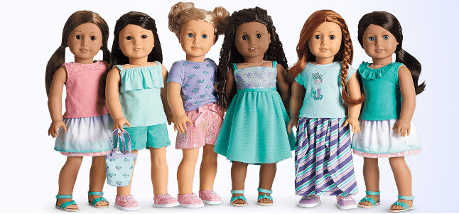 [Image Description: Six American Girl Dolls standing side by side. From Left to Right: Doll with tan skin and straight brown hair in low pig tails wearing a pink sleeveless shirt, a turquoise and pink skirt, and turquoise sandals. The second doll from the left is asian-coded. They have long black straight hair, and are wearing a mint-colored tank top, turquoise shorts, pink shoes, and holding a mint colored bag with floral detailing. The next doll has light skin and blonde hair done up in two high buns. They are wearing a purple t-shirt with floral dealing, pink shorts, and pink shoes. The third doll from right has medium brown skin and long curly dark brown hair. They are wearing a blue and turquoise dress with turquoise sandals. The second doll from right has light skin and long straight red hair with a single braid in the front. They are wearing a mint-colored shirt and a long purple, pink, and mint striped skirt with pink shoes. The doll on the far right has tan skin and straight brown hair in a side pony tail. They are wearing a turquoise tank top with a ruffle at the top, a white, mint., and pink skirt, and turquoise sandals.]