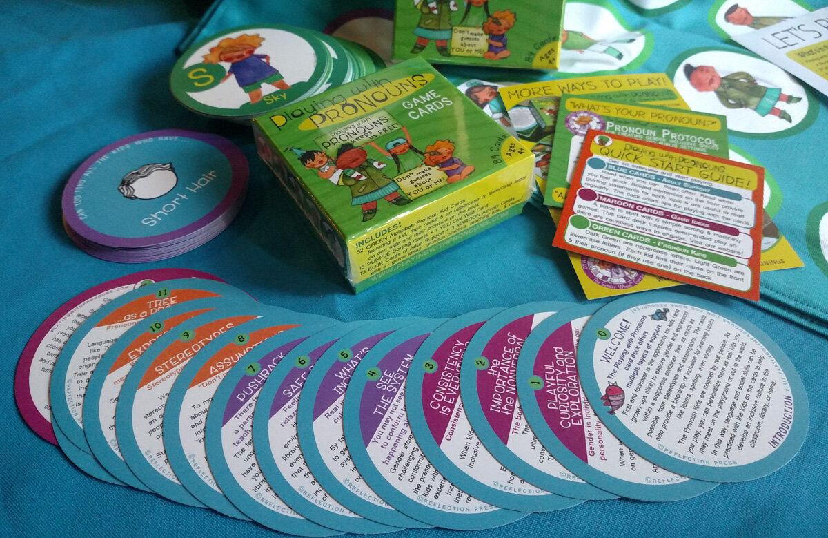 [Image Description: A set of Playing With Pronouns cards scattered across the table with the green box they come in. The cards are circular and feature tex that is indecipherable in the photo.]