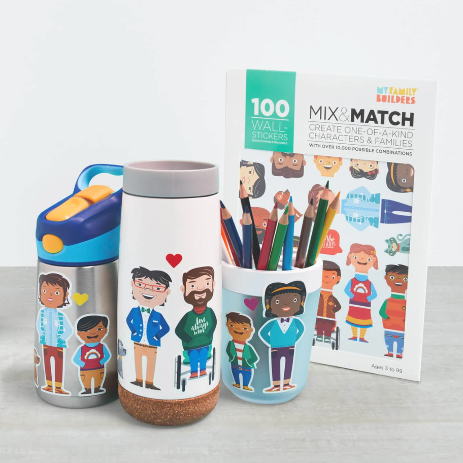 """[Image Description: A set of stickers that reads """"100 Wall Stickers My Family Builders Mix and Match Create One-Of-A-Kind Characters and Families"""" There are also two water-bottles and a cup filled with pencils featuring the stickers with people of varying abilities, skin tones,, and hair colors as well as varying family make-ups.]"""