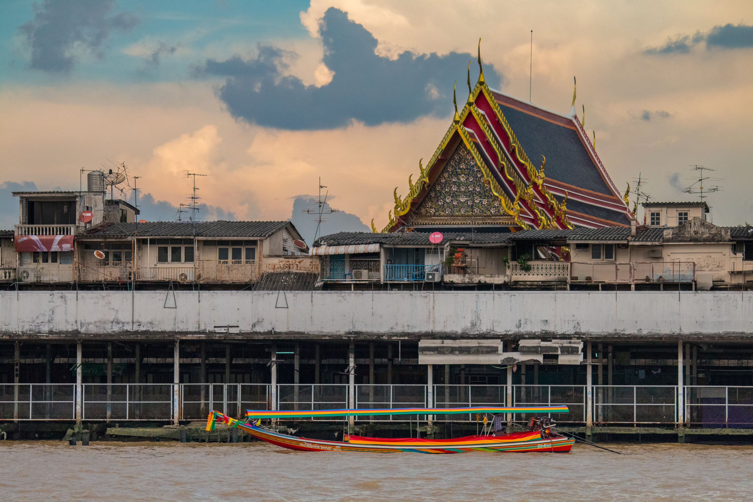 River boat on Chao Phraya River with Wat Pho in the background, Bangkok, Thailand.