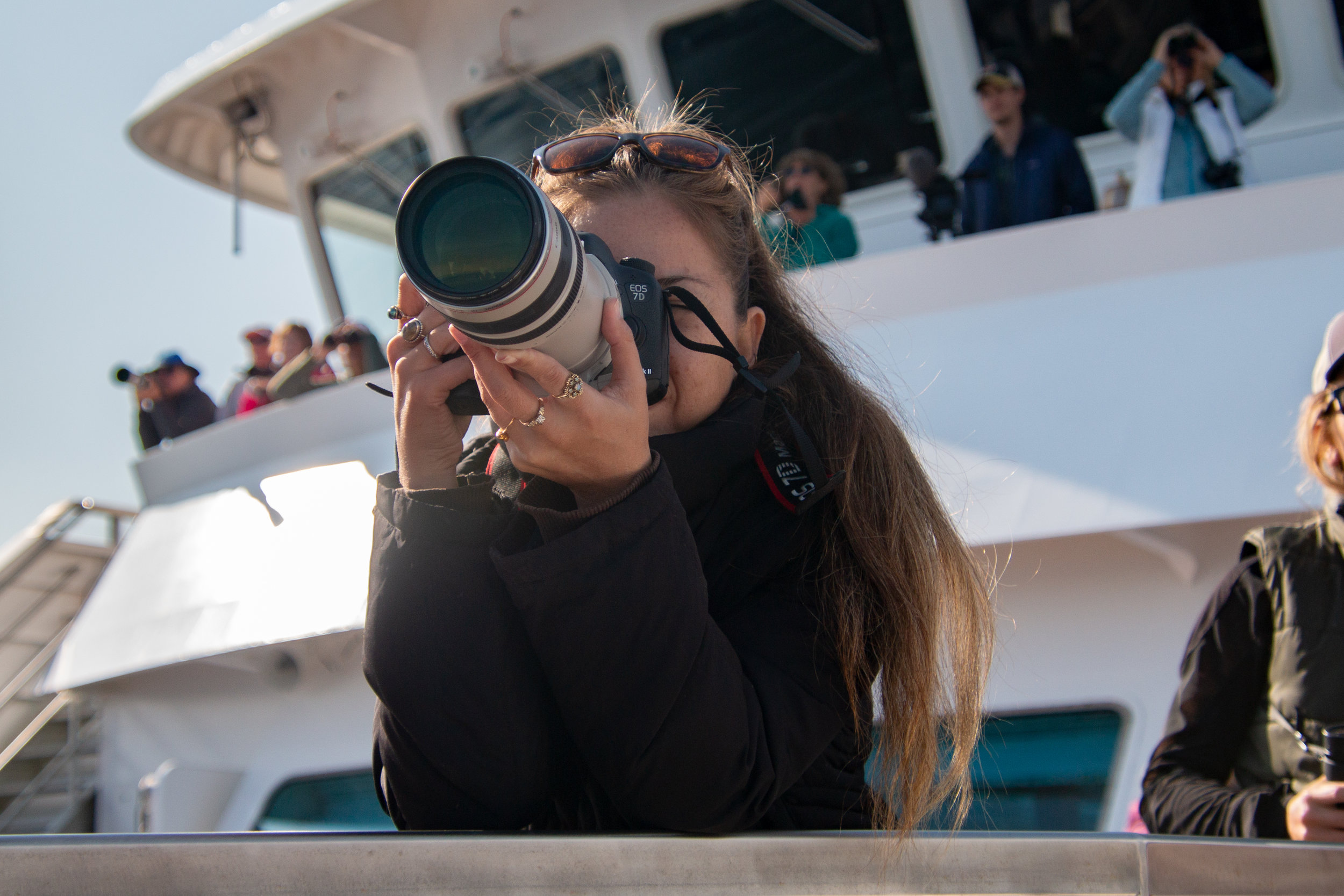 Photographer taking shots off the bow of National Geographic Venture, Chatham Strait, Southeast Alaska.
