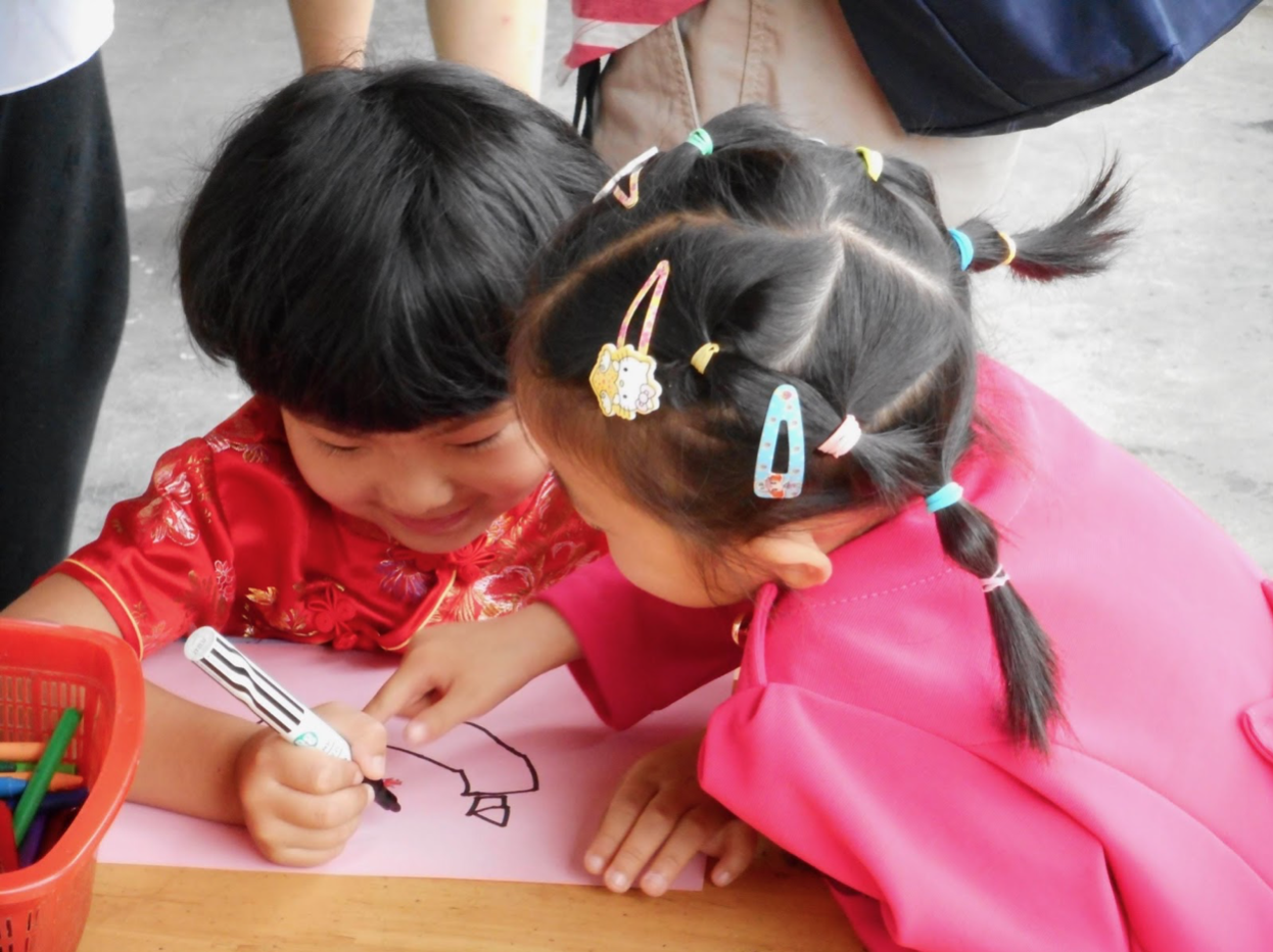 Peter Mangione: This photo shows one child drawing a play story, with a second child communicating with her about details in the drawing. The intent engagement of the two children as they collaboratively reflect on their play is one of the countless powerful learning experiences that I have observed in the Anji kindergartens.