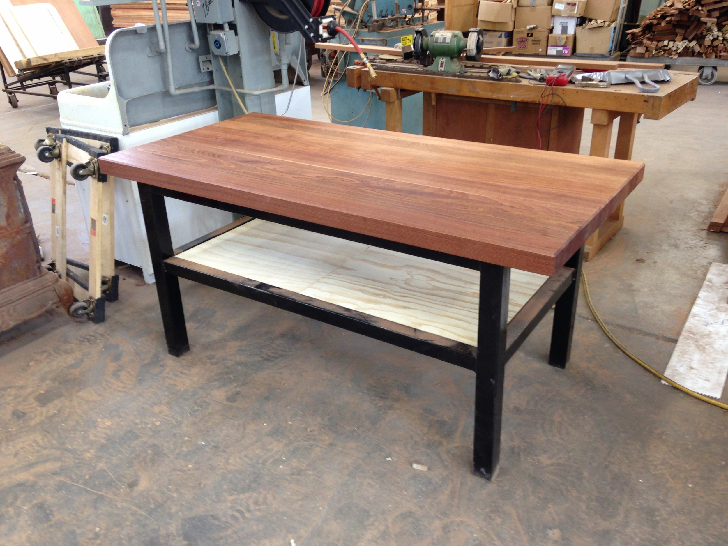This is a Sapele Mahogany top with welded mild steel legs and structure.  We can do items of this variety with specific size and shape for a price competitive with furniture stores.  The top could be oak, reclaimed pine, cypress, or walnut flitch, all of which we stock.  Probably the best value we can offer in a custom furniture piece.