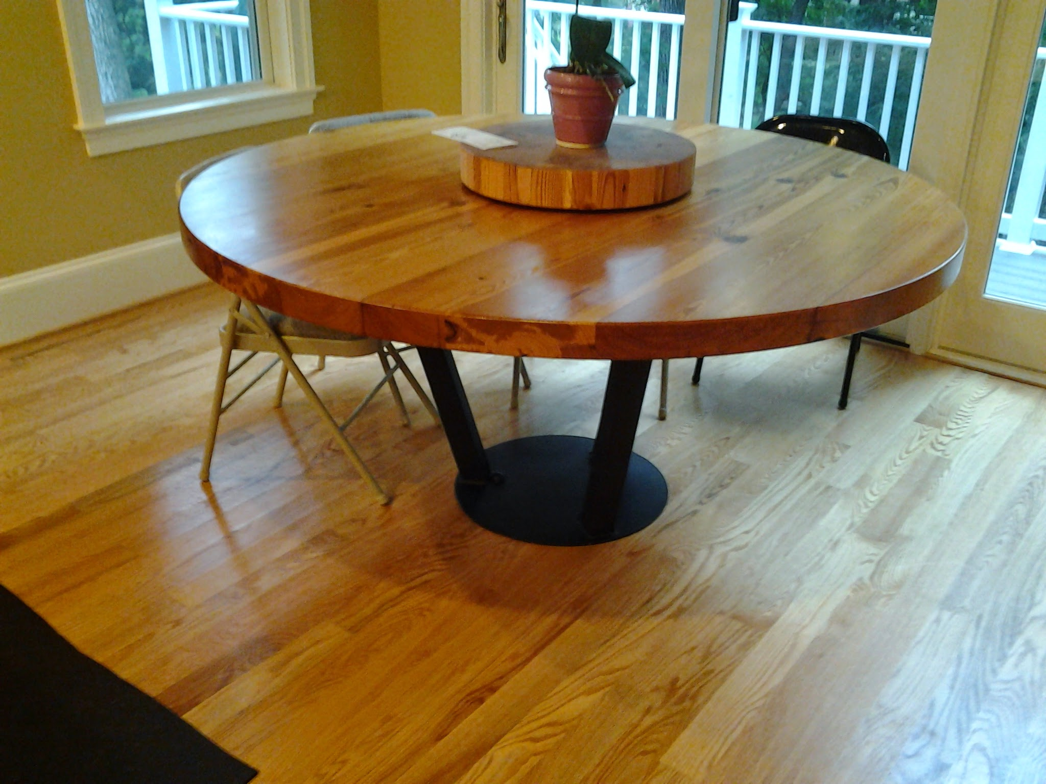 The top is reclaimed pine first cut in the early 19th century.  A round table can make for very efficient use of a small dining room.  For this style base, the piece is bolted to the architecture.