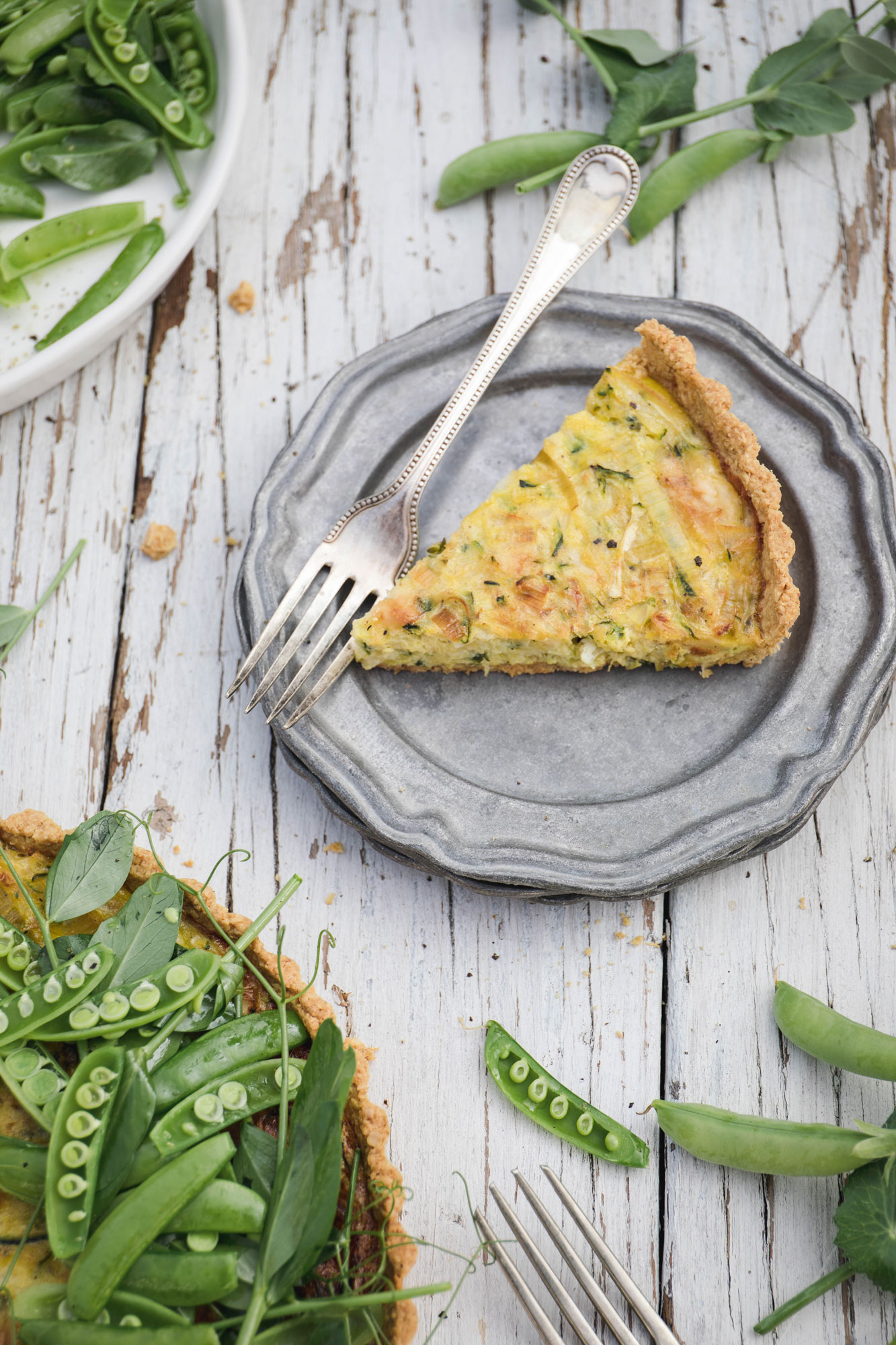 Gluten free summer picnic tart with leek, sharp cheddar and zucchini. Topped with snap pea salad.