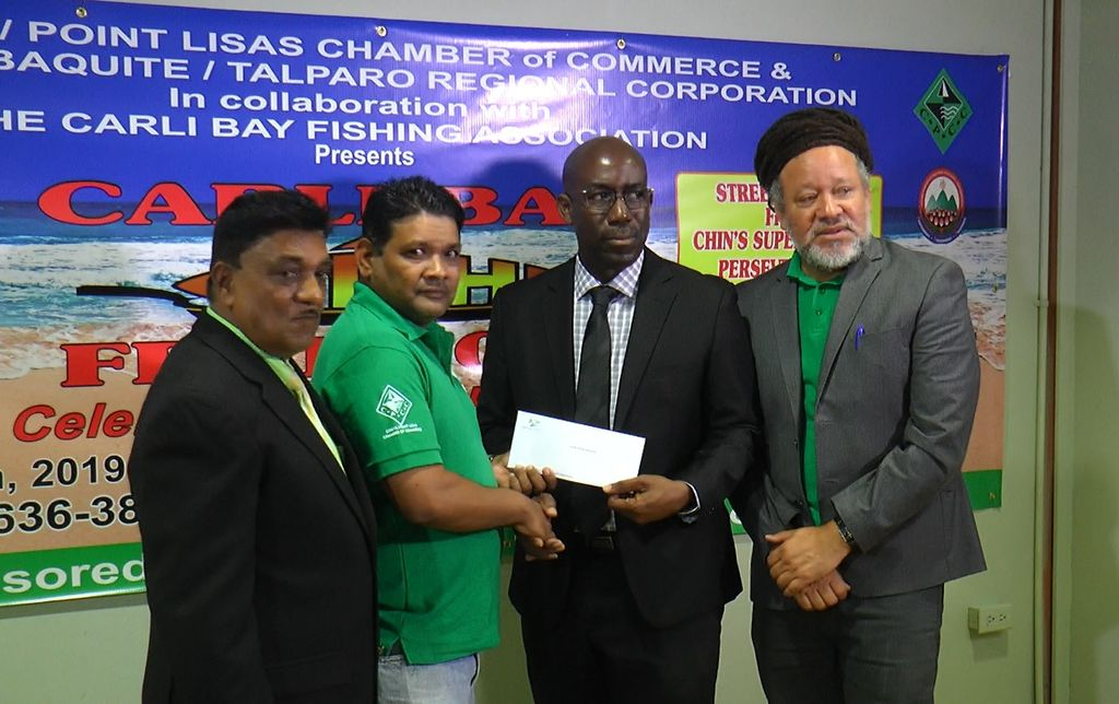 The Proman Group present a cheque to the organisers of the Carli Bay Fish Festival.