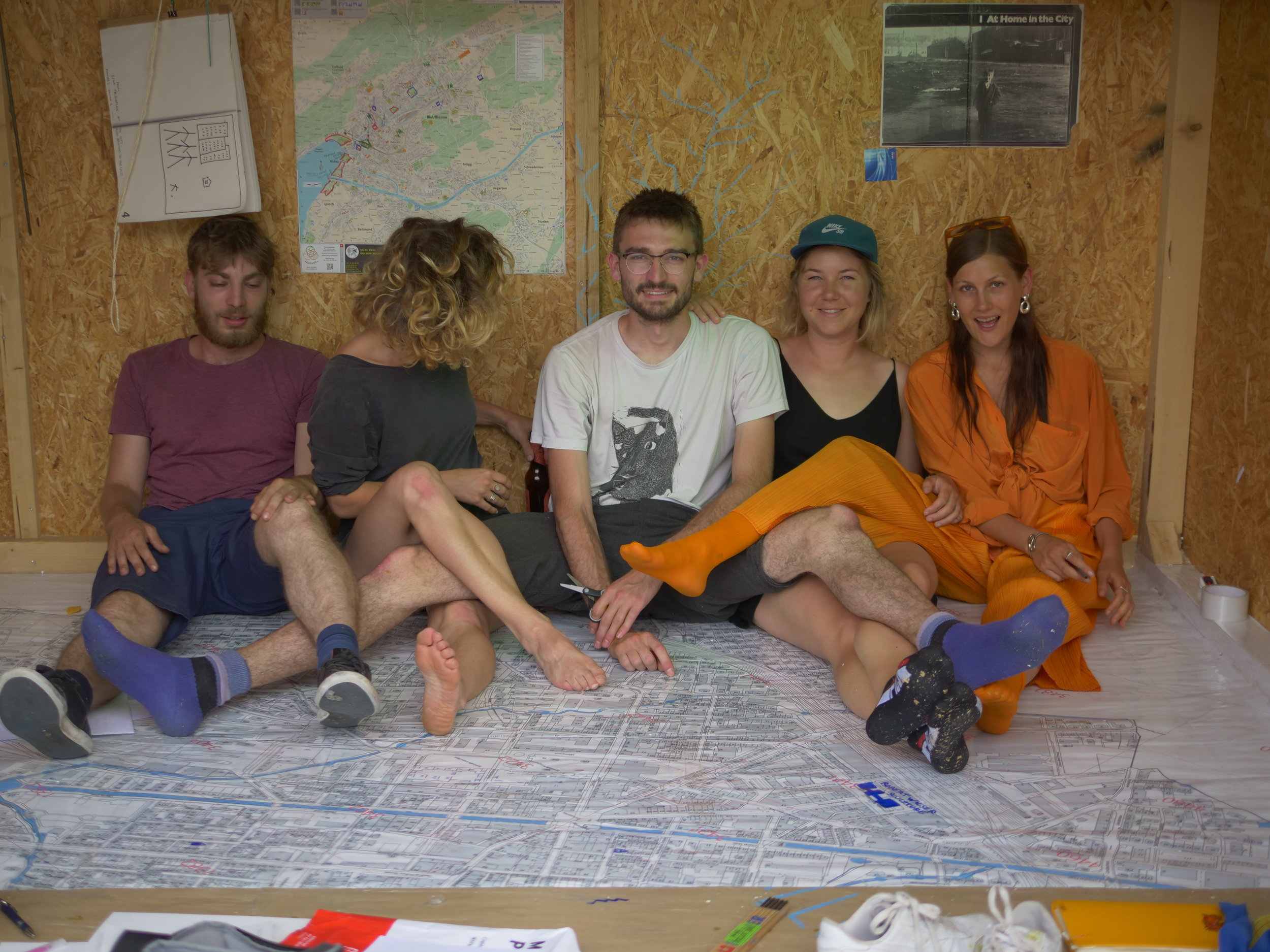 - Part 2Our last day altogether is saturated with enthusiasm, primarily about finishing the map on the floor. We begin to work on it upon arrival, catch on taking charge of specific corner or space, being mindful of each others bodies in the already small space.Charles and I begin a method where I plastify after he lays down the papers and it works well, albeit tedious. Delphine arrives and suggests we plastify together dissecting the action into tasks we each commit to, rendering it into a dance. We stretch, turn, twist, our bodies around the space sliding into a beautiful yet very interruptible rhythm. Think about the inherent choreographies of collective work that transpires when two bodies do something one body can do. It is this micro action that leads me to reflect upon the dynamism of the group, and how intricate the dance has become, a polyphonic entity that has just arrived in Bienne to sing its 86 day long hymn.