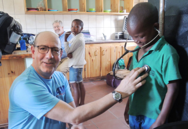 Dr. Rob Zimmerman does basic checkups while Dr. Bob Wenz (background) does eye checks for the children at the St. Camillus Centre.